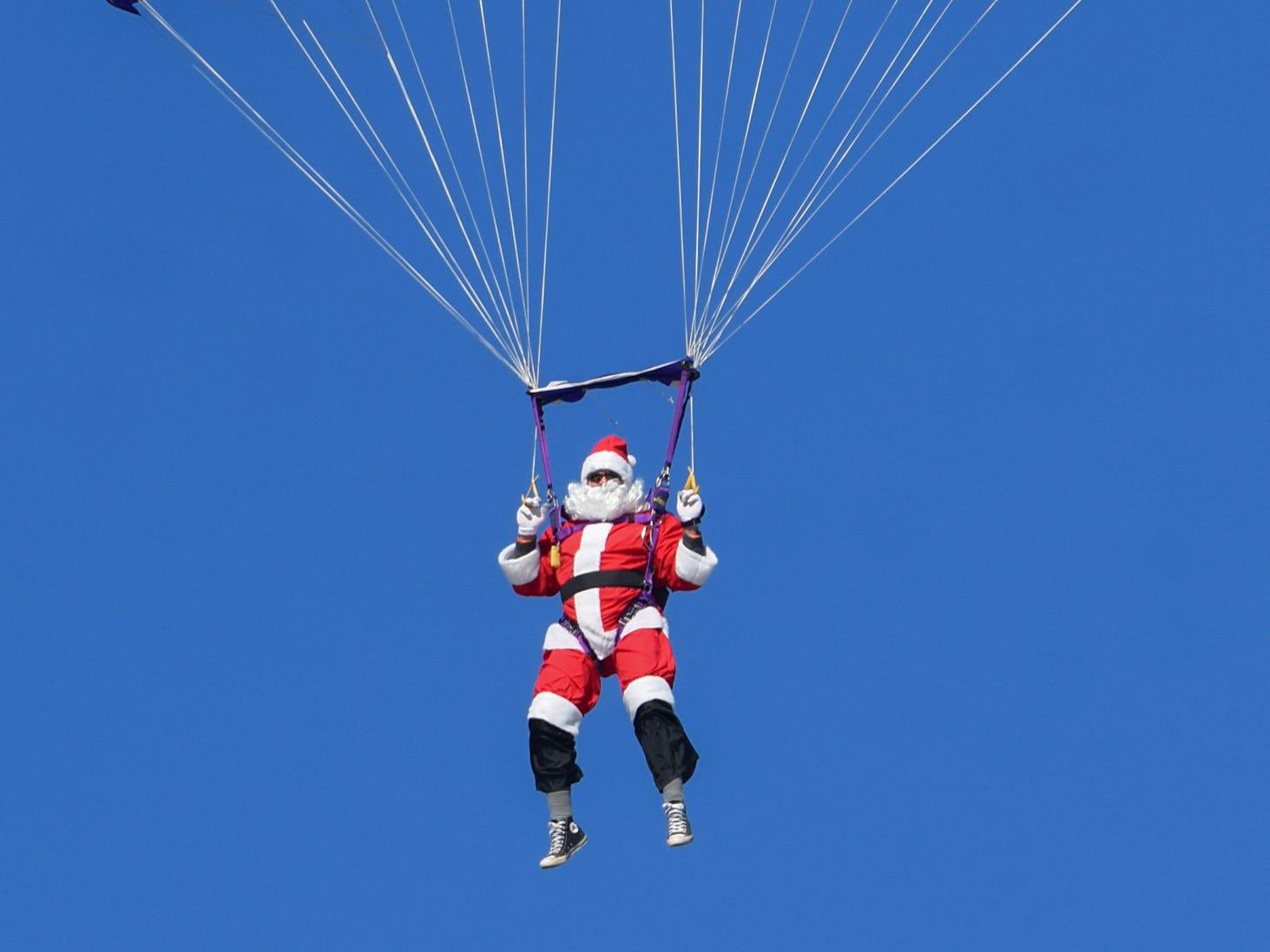 Chuck Bigler, dressed as Santa Claus, makes his way for a landing during the annual Santa Drop at Veterans Memorial Stadium in Shenandoah, Pa., on Friday, Nov. 23, 2018.