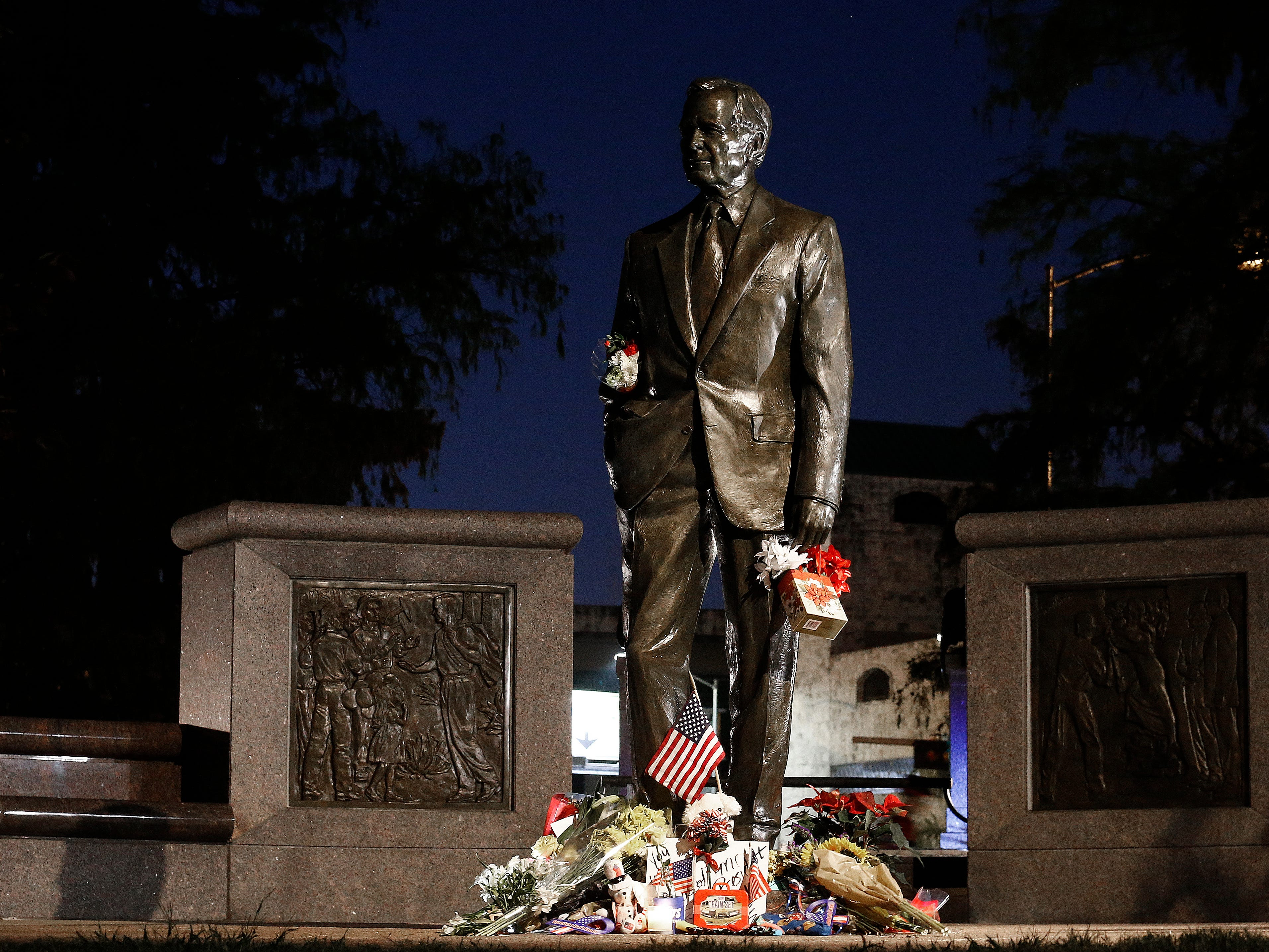 A statue of George H.W. Bush with flowers stands near downtown in Houston, Dec. 2, 2018.