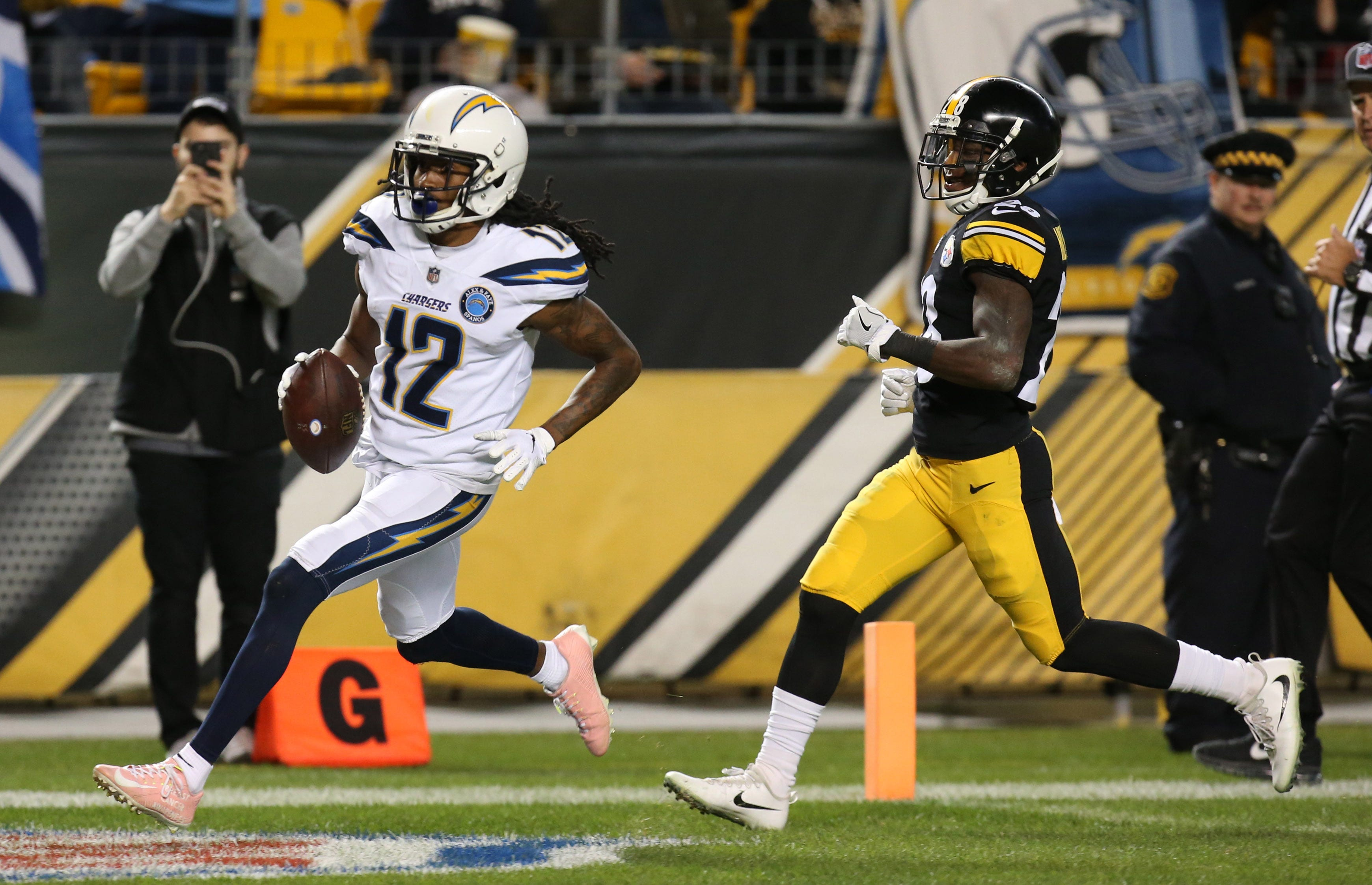 Los Angeles Chargers wide receiver Travis Benjamin (12) scores a touchdown past Pittsburgh Steelers cornerback Mike Hilton (28) during the first quarter at Heinz Field.