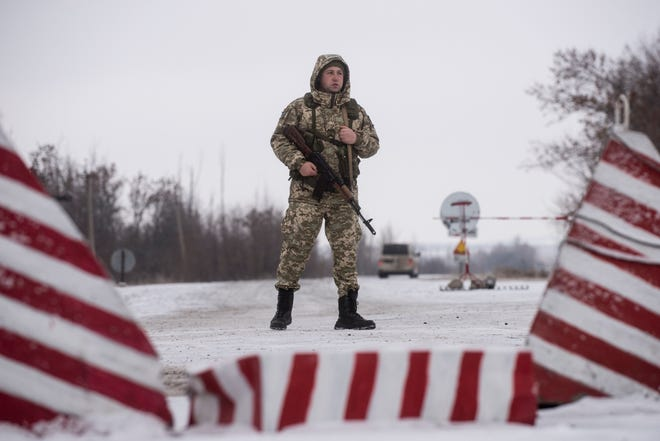 A Ukrainian border guard stands ready at the border from Russia to Ukrainian side of the Ukraine - Russia border in Milove town, eastern Ukraine, Sunday, Dec. 2, 2018. On a map, Chertkovo and Milove are one village, crossed by Friendship of Peoples Street which got its name under the Soviet Union and on the streets in both places, people speak a mix of Russian and Ukrainian without turning choice of language into a political statement.