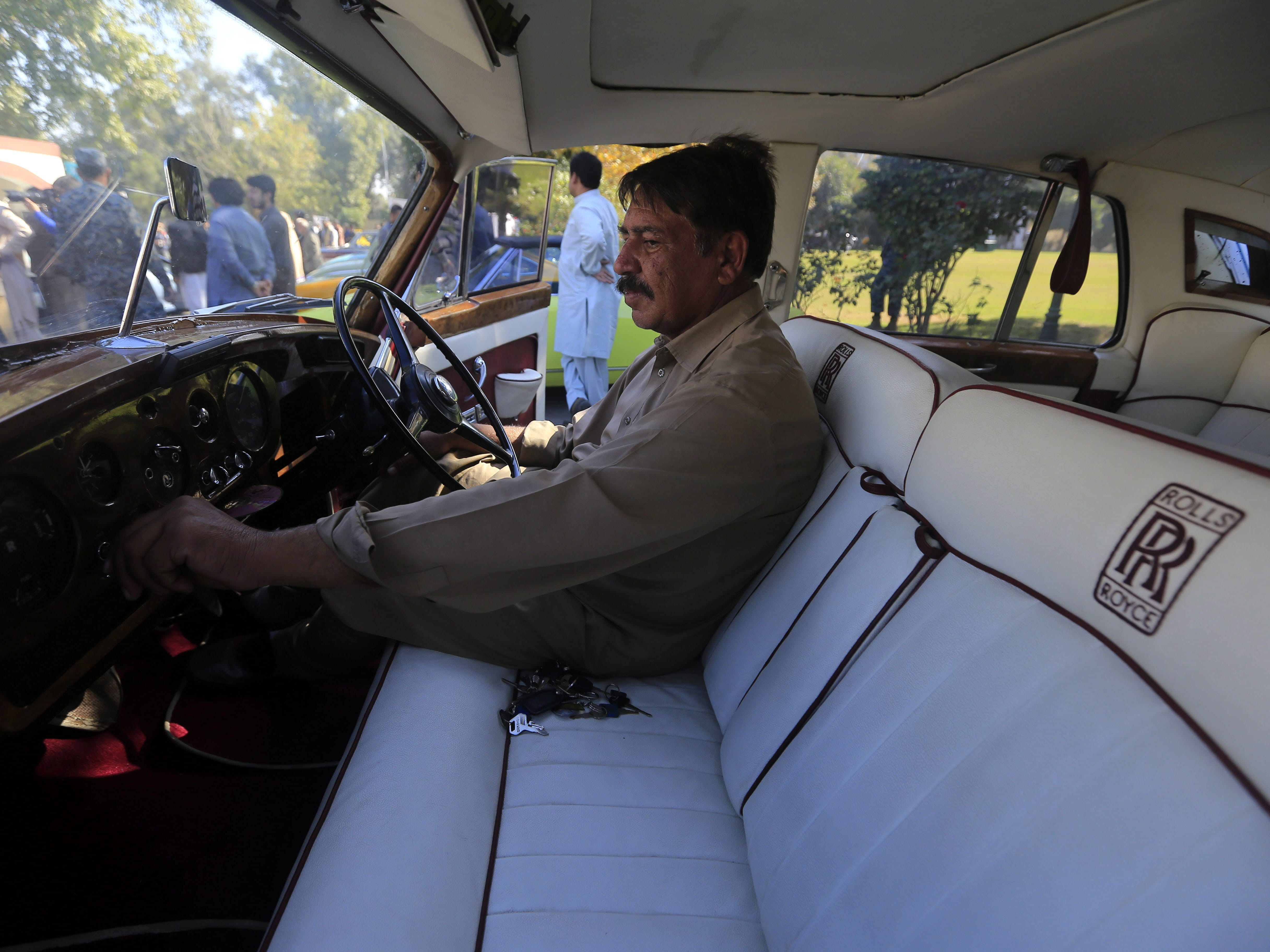 epa07185127 A man sits inside a Rolls Royce oldtimer on display during a show organized by the Vintage and Classic Car Club of Pakistan in Peshawar, Pakistan, 23 November 2018. More than 60 vintage and classic cars were on display from all across Pakistan, some coming all the way from Karachi and heading on to Khyber.  EPA-EFE/BILAWAL ARBAB ORG XMIT: PSH01