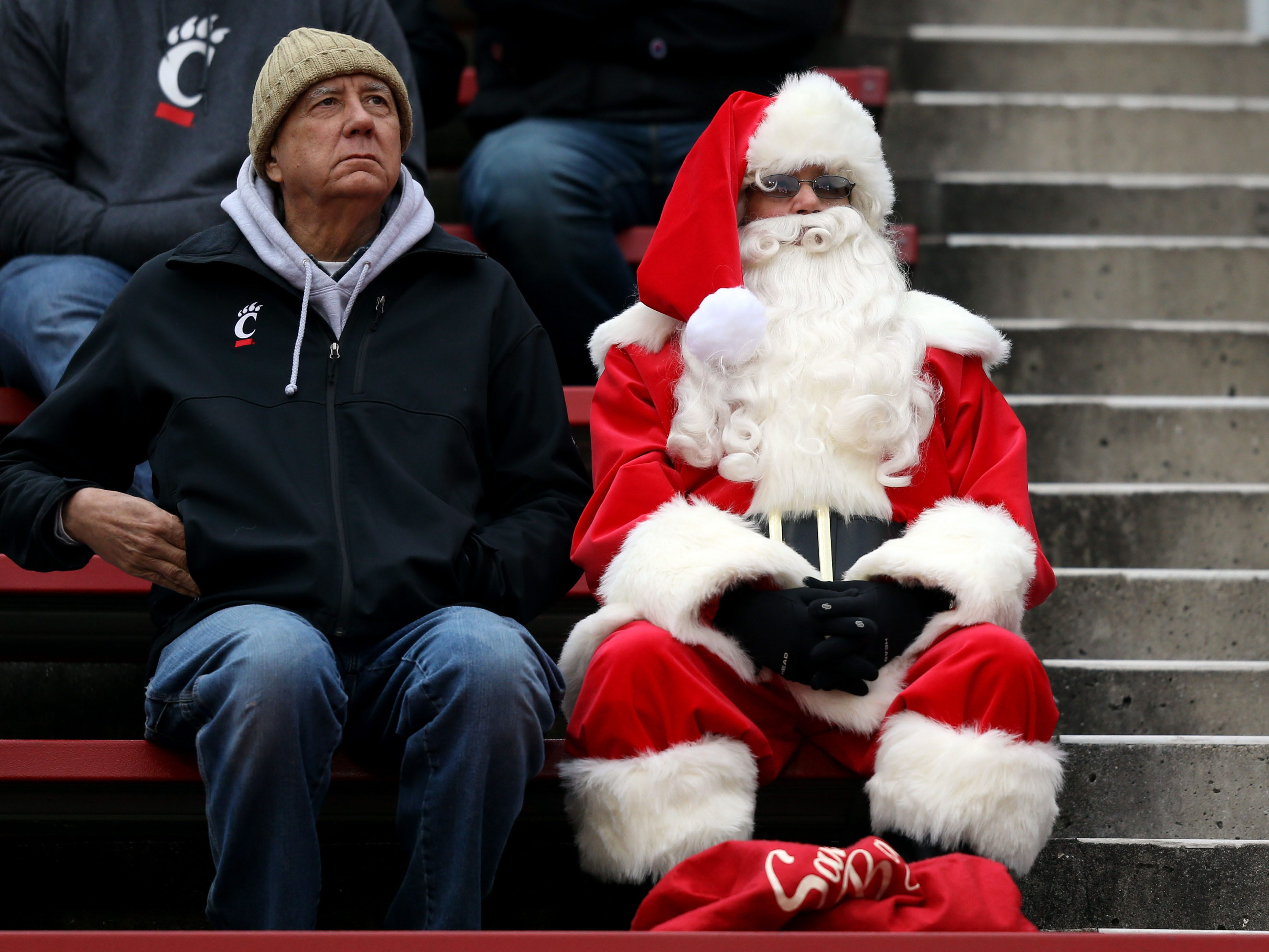 A fan dressed as Santa Claus sits in the stands during the game between the East Carolina Pirates and the Cincinnati Bearcats in Cincinnati, Ohio, Nov. 23, 2018.