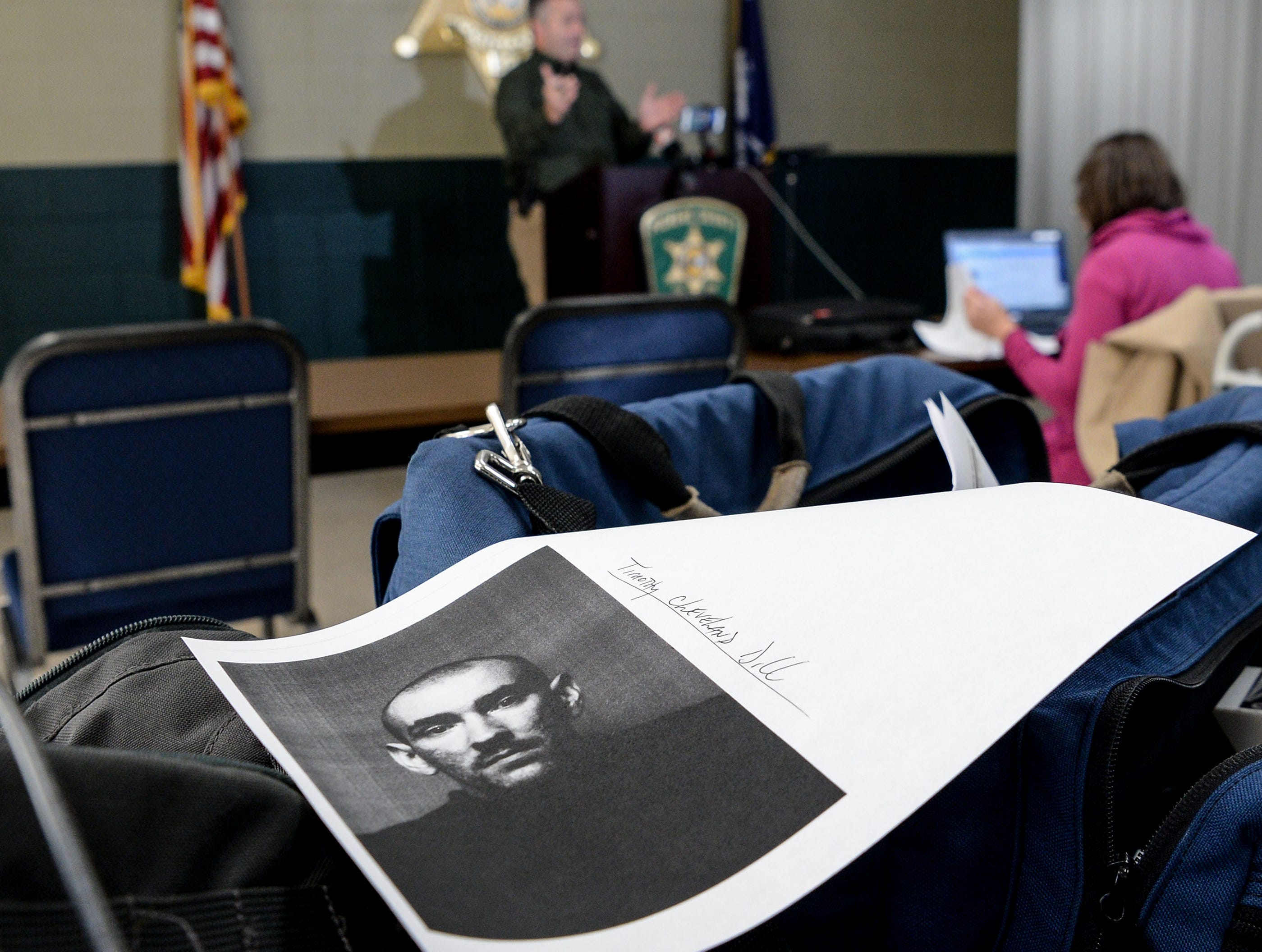 A printed photo of Timothy Cleveland Dill on a table while Pickens County Sheriff Rick Clark speaks to media about two inmates who escaped from the Pickens County Detention Center early Tuesday morning.