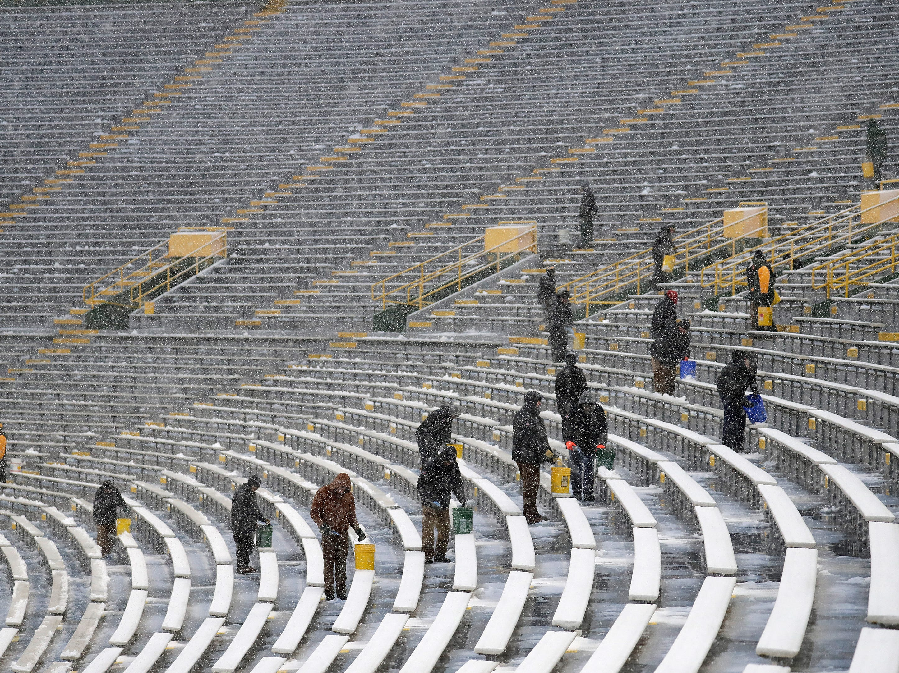 Workers spread salt and clear snow from benches in the seating area before the Green Bay Packers play against the Arizona Cardinals Sunday, December 2, 2018, at Lambeau Field in Green Bay, Wis. 