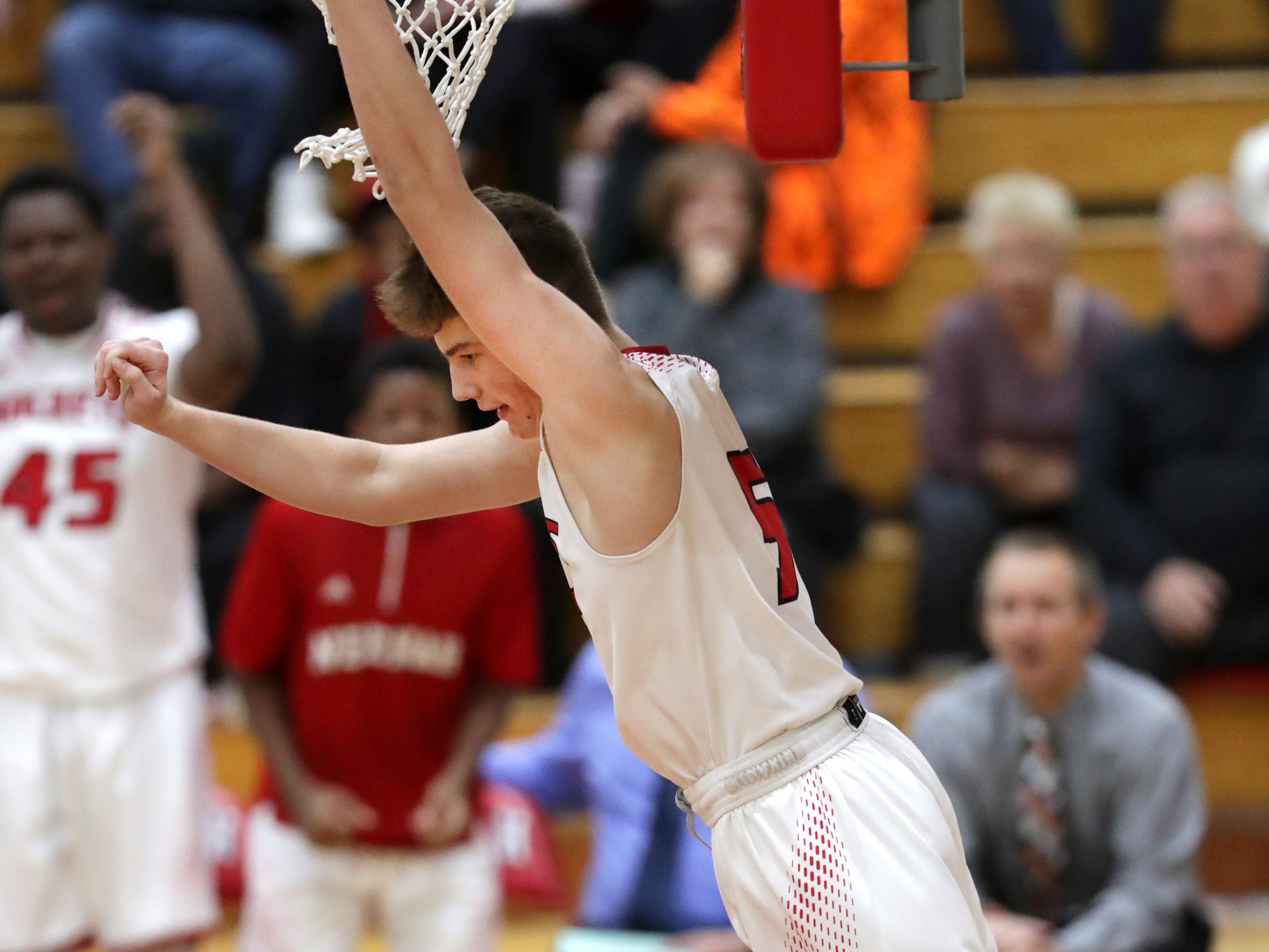 Neenah High School's #5 Max Klesmit  hangs from the rim against Hortonville High School during their Fox Valley Association boys basketball game on Friday, November 30, 2018, in Neenah, Wis. Neenah defeated Hortonville 71 to 67 in overtime.