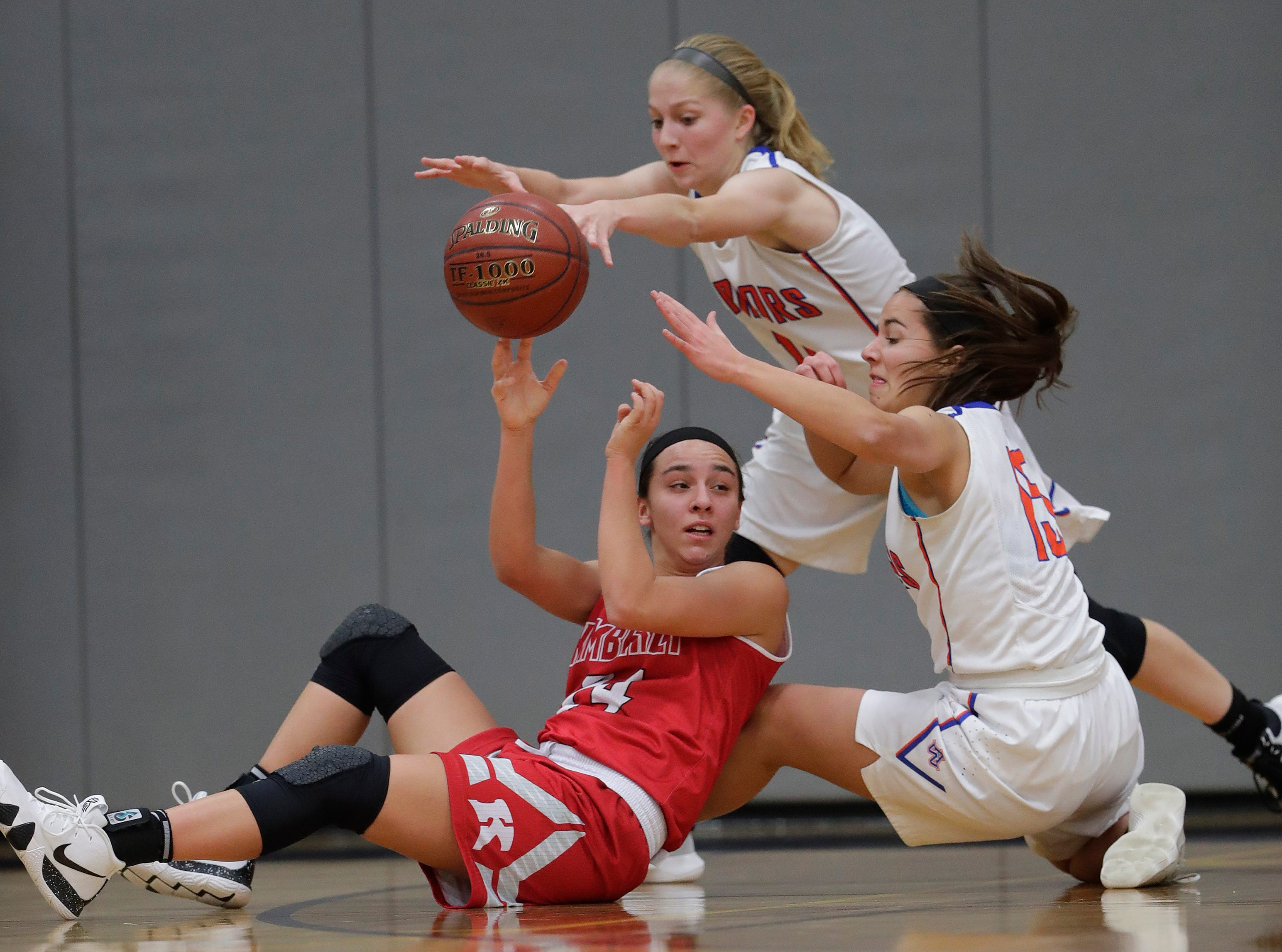 Kimberly High School's Shea Dechant (24) passes the ball under heavy pressure from Appleton West High School's Jamie Winsted (11) and Addie Pauling (15) during their girls basketball game Tuesday, November 27, 2018, in Appleton, Wis. 