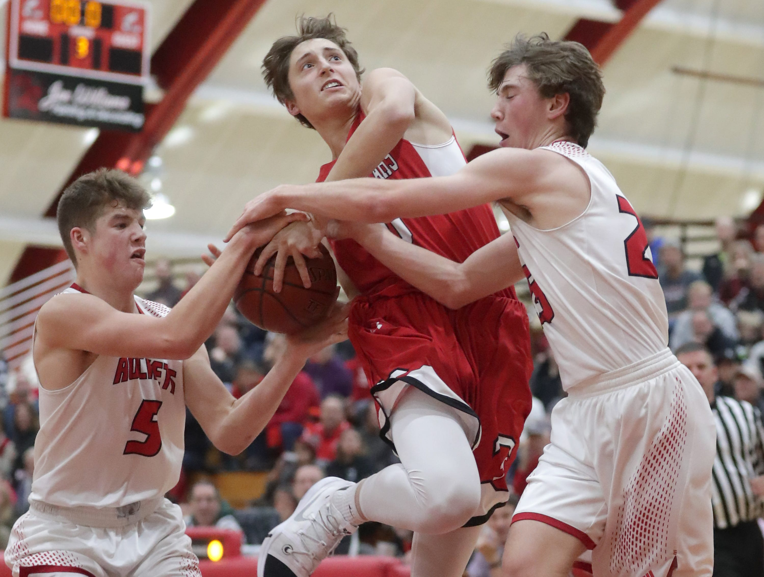 Hortonville High School's #10 Mason Thiel against Neenah High School's #5 Max Klesmit and #25 Bryce Henderson during their Fox Valley Association boys basketball game on Friday, November 30, 2018, in Neenah, Wis. Neenah defeated Hortonville 71 to 67 in overtime.
