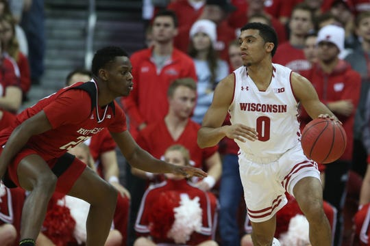 Wisconsin Badgers guard D'Mitrik Trice (0) looks to pass as Rutgers Scarlet Knights guard Montez Mathis (23) defends.