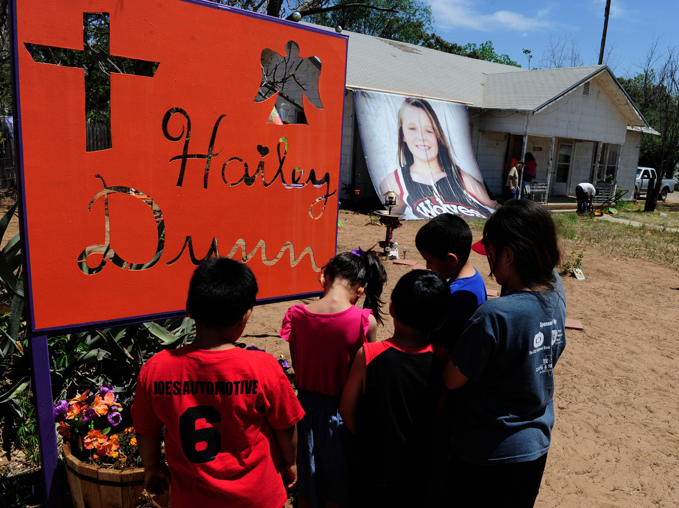 A group of Colorado City schoolchildren bow their heads in front of a memorial sign and flowers in the front yard of Hailey Dunn's former home.