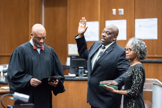 Quentin Miller is joined by his wife Karen Sconiers as he is sworn in as the new Buncombe County Sheriff by Chief District Court judge Calvin Hill Dec. 3, 2018.