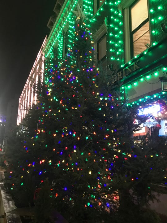 A towering Christmas tree stands outside of The Colonial in downtown Binghamton during the holiday season.