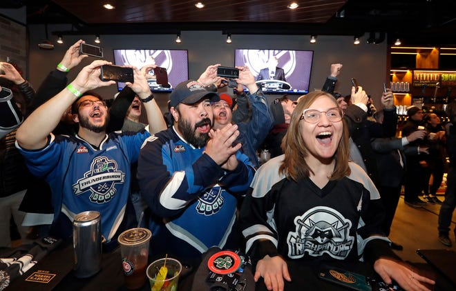 Ryan Kelly, left, Otto Rogers and Rebecca Moloney cheer the announcement of a new NHL hockey team in Seattle at a celebratory party Tuesday, Dec. 4, 2018, in Seattle. The NHL Board of Governors unanimously approved adding Seattle as the league's 32nd franchise on Tuesday, with play set to begin in 2021 to allow enough time for arena renovations.