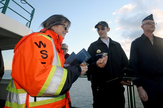Washington State Ferries workers Donna Phillips, left, of Port Orchard, and James Patheal, center, of Bremerton, look at Coast Guard coins awarded to them on Monday. They were honored for saving a man they found in the ferry lane in Sinclair Inlet in August.