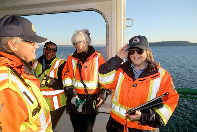 Washington State Ferries worker Donna Phillips, right, of Port Orchard, puts on her life ring hat she was awarded on Monday. She was one of two WSF workers honored for helping to save a man they found in the ferry lane in Sinclair Inlet in August.