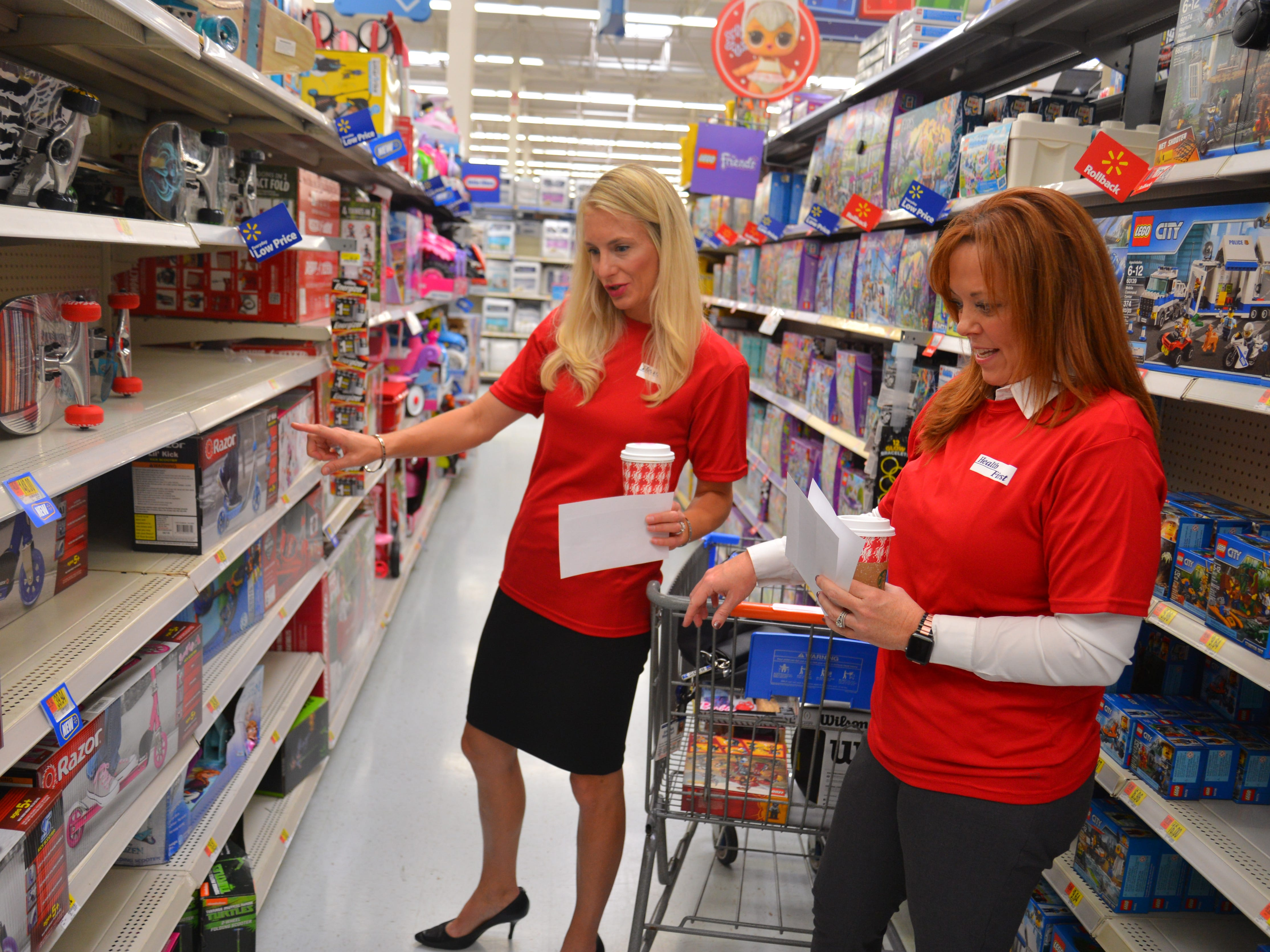 "Shana Marshall and Michelle Murhpy search for specific toys. For the sixth year in a row, Health First partnered with the South Brevard Sharing Center to help fulfill wish lists for children who might not receive gifts for the holidays. On Tuesday morning 80 Health First associates in red shirts and volunteers from the South Brevard Sharing Center  descended on Walmart in Viera to purchase gifts for more than 600 children in Brevard County — many of whom are homeless — as part of the Sharing Center's ""Children Without Christmas Toy Drive."""