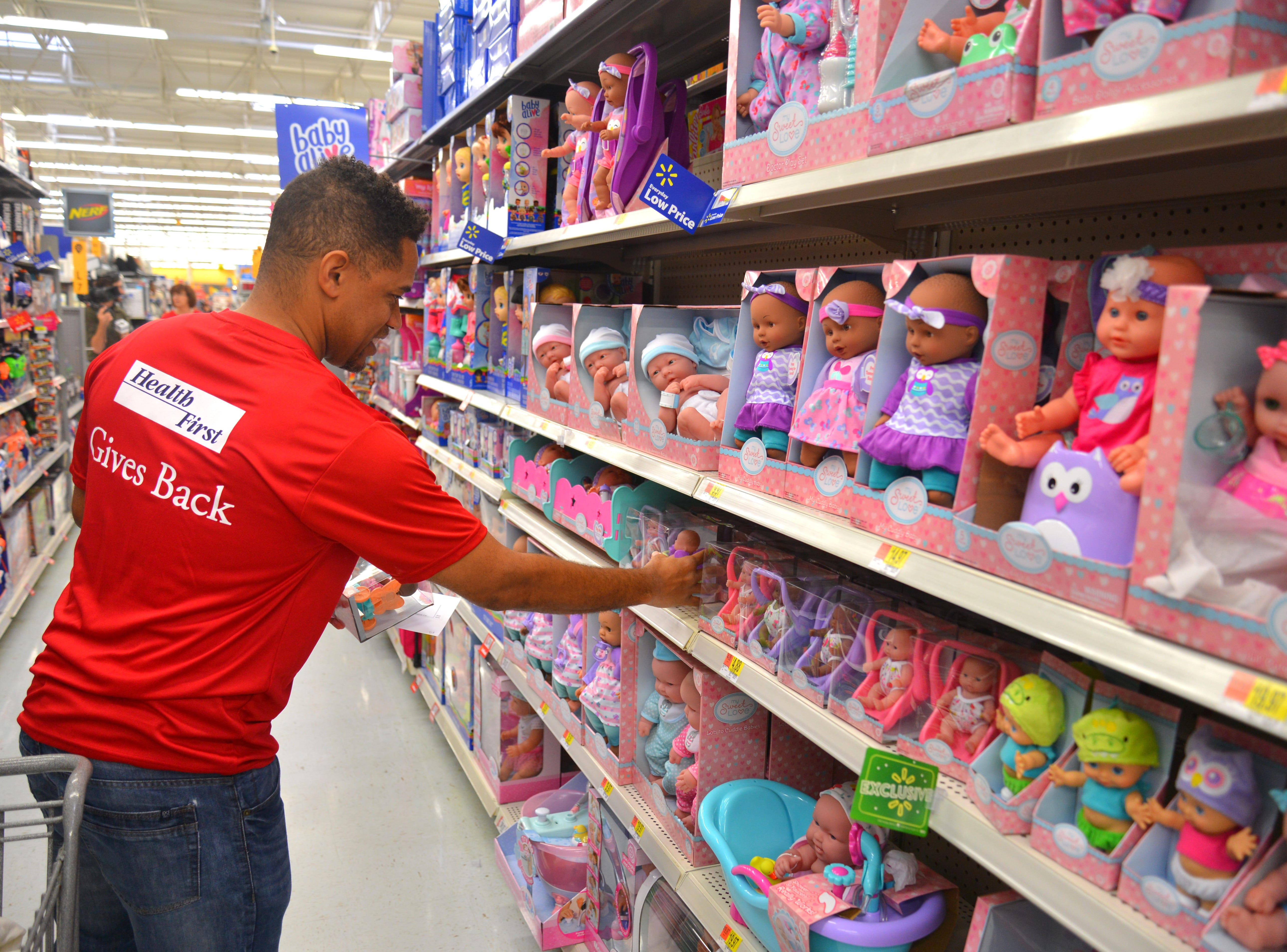 "George Tennort buys a doll for a little girl. For the sixth year in a row, Health First partnered with the South Brevard Sharing Center to help fulfill wish lists for children who might not receive gifts for the holidays. On Tuesday morning 80 Health First associates in red shirts and volunteers from the South Brevard Sharing Center  descended on Walmart in Viera to purchase gifts for more than 600 children in Brevard County — many of whom are homeless — as part of the Sharing Center's ""Children Without Christmas Toy Drive."""