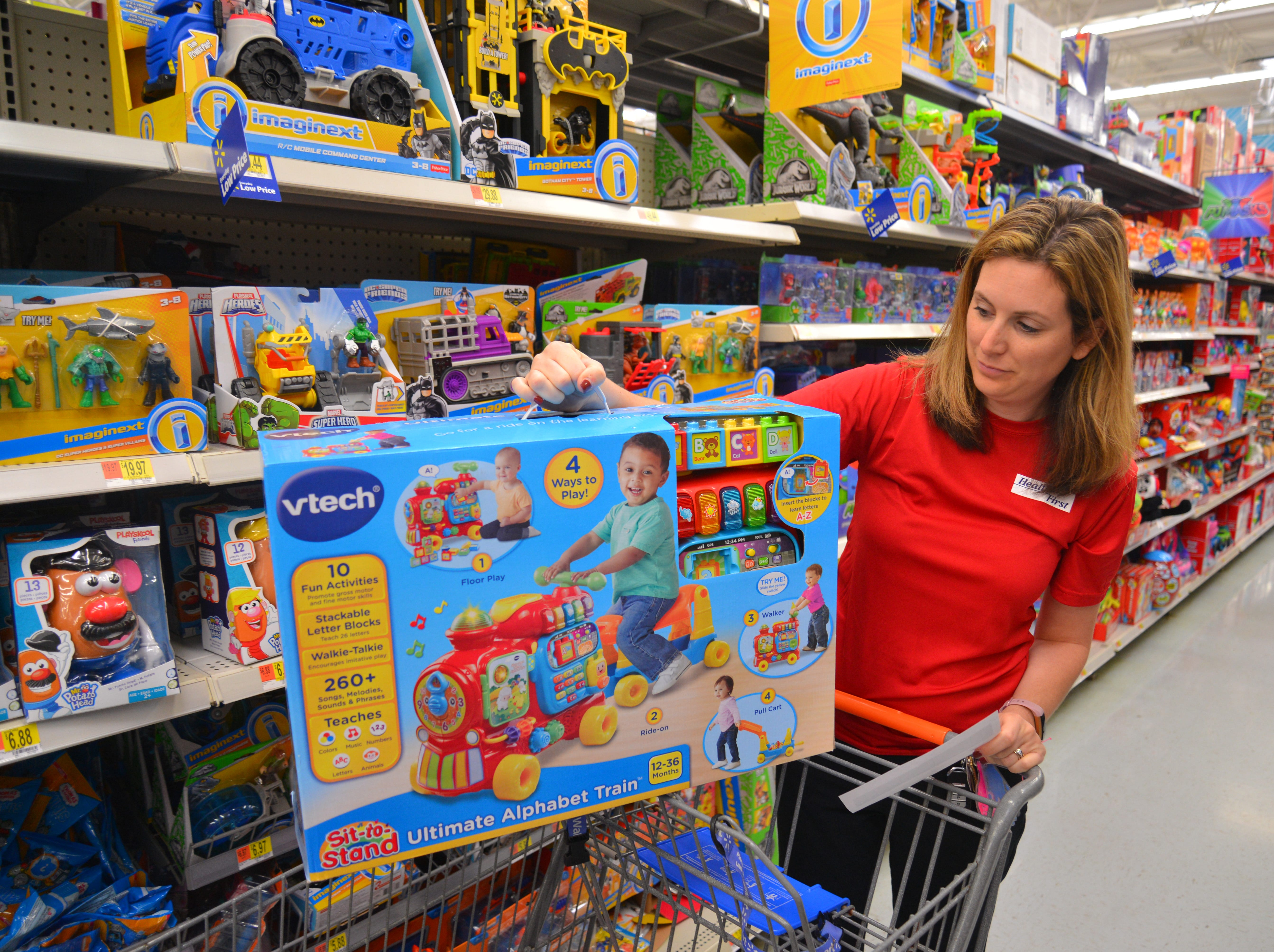 "Emily Suttles loads a V-Tech train into her cart. For the sixth year in a row, Health First partnered with the South Brevard Sharing Center to help fulfill wish lists for children who might not receive gifts for the holidays. On Tuesday morning 80 Health First associates in red shirts and volunteers from the South Brevard Sharing Center  descended on Walmart in Viera to purchase gifts for more than 600 children in Brevard County — many of whom are homeless — as part of the Sharing Center's ""Children Without Christmas Toy Drive."""