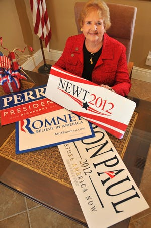 Barbara Davis, who as the time was chair of the Brevard Republican Executive Comittee, with signs of some of the Republican candidates for president in 2012.