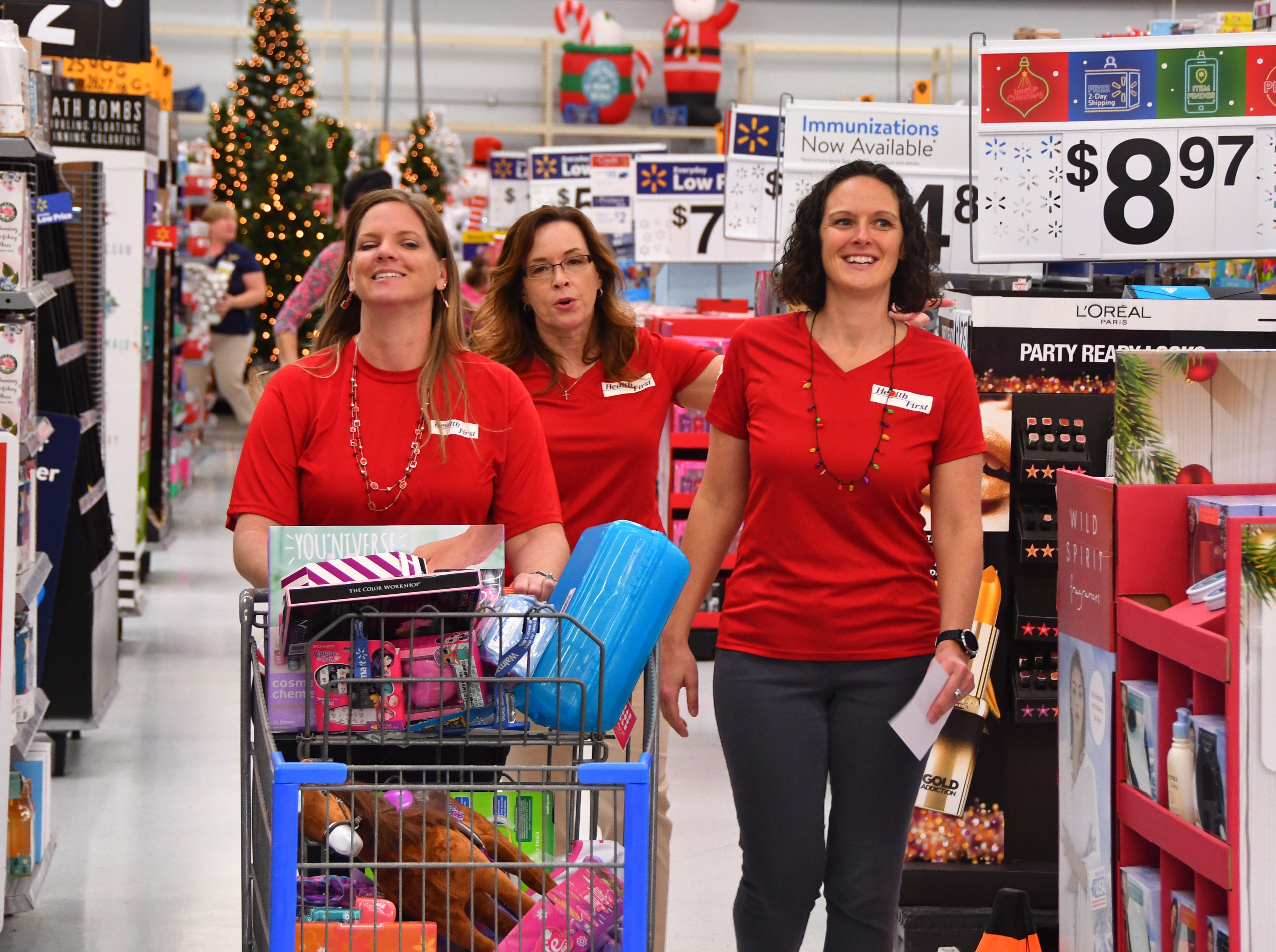 "This team of shoppers, Patti Canitano, Diana Nugent and Liz Taylor, had a cart full of toys for kids. On Tuesday morning 80 Health First associates in red shirts and volunteers from the South Brevard Sharing Center  descended on Walmart in Viera to purchase gifts for more than 600 children in Brevard County — many of whom are homeless — as part of the Sharing Center's ""Children Without Christmas Toy Drive."""