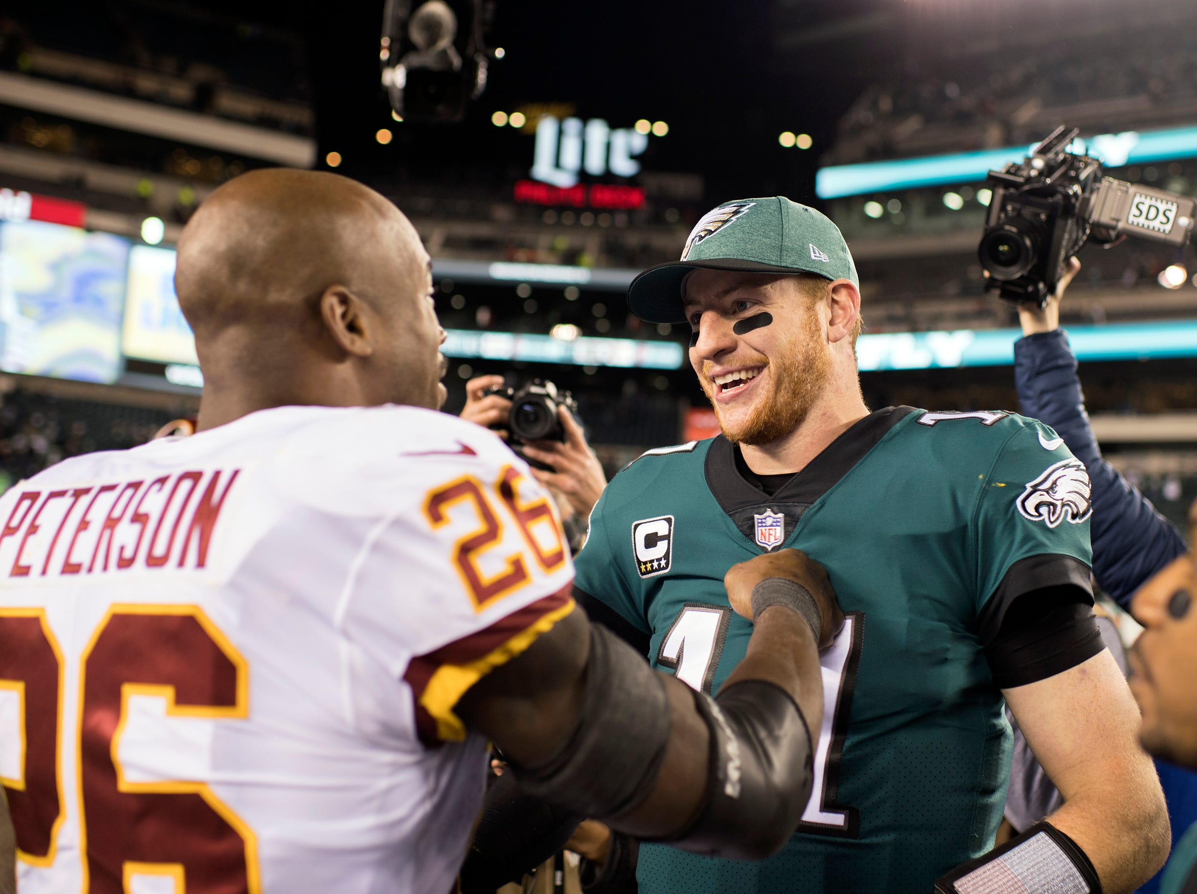 Eagles' Carson Wentz and Redskins' Adrian Peterson greet each other after a game Monday, Dec. 3, 2018 in Philadelphia. The Eagles won 28-13.