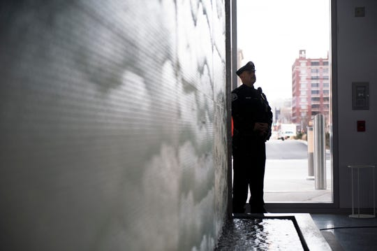 A police officer stands by a waterfall wall in the entranceway while American Water celebrates its grand opening Tuesday, Dec. 4, 2018 in Camden, N.J.