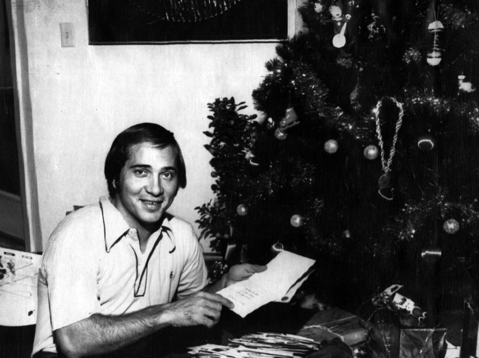 """DECEMBER 23, 1972: Cincinnati Res catcher John Bench, recovering from surgery about two weeks ago, points to a Christmas card he received from President Nixon. The card, which contained no personally-written message, was one of thousands of Christmas cards and """"get well"""" wishes sent to Bench since he had a benign spot removed from one lung. Doctors say he will play as usual this spring. AP Photo scanned August 8, 2013 FROM A SUNDAY DECEMBER 24, 1972 ARTICLE BY BILL WINTER, ASSOCIATED PRESS SPORTS WRITER: 'Dear Johnny Bench...': One insistent young miss who wrote to Johnny Bench following the Cincinnati slugger's recent surgery spoke for most of the 15,000 who sent letters. """"I love you Johnny Bench,"""" the little girl wrote. """"You are a good baseball player. You are a good man. I love you. Do you love me? Yes or no? Write back!"""" Recovering from surgery during which a benign lesion was removed from his right lung, Bench still is struggling through a mountain of such mail. Ted Bench, the young catcher's father, is helping, as is Mrs. Bench. """"It's unbelievable,"""" the elder Bench said as he sifted through seven boxes of unopened mail. """"They're from everywhere, from Hawaii, Puerto Rico, from all over. It is something else."""" The younger Bench, most valuable player in the National League two of the last three seasons, mused over the outpouring of good will."""