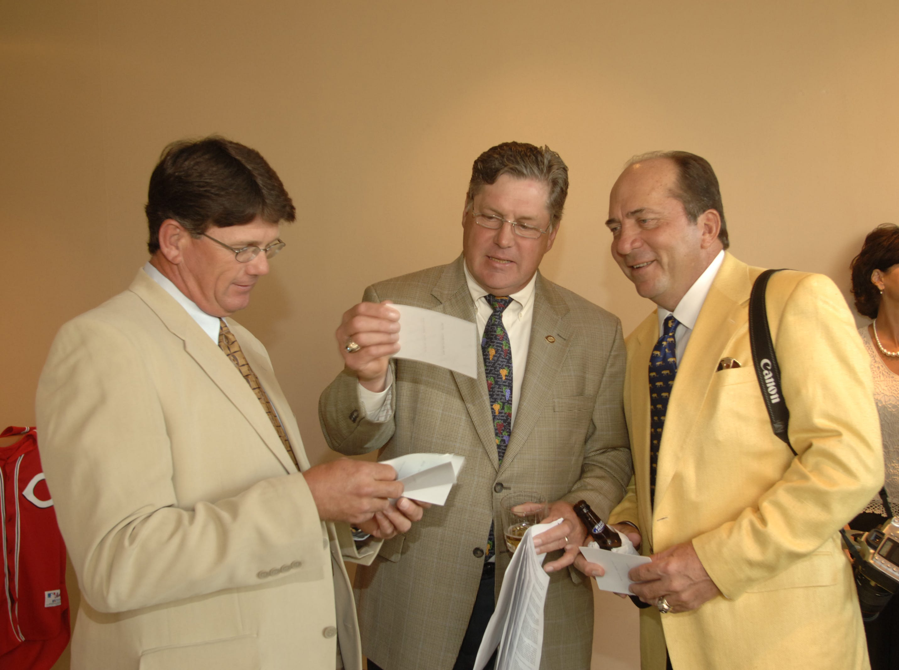 Proud Papa, Johnny Bench (right), shows pictures of his newborn son, Justin Palmer Bench, to Reds pitching coach, Tom Hume (left), and new member of the Reds Hall of Fame, Tom Seaver.