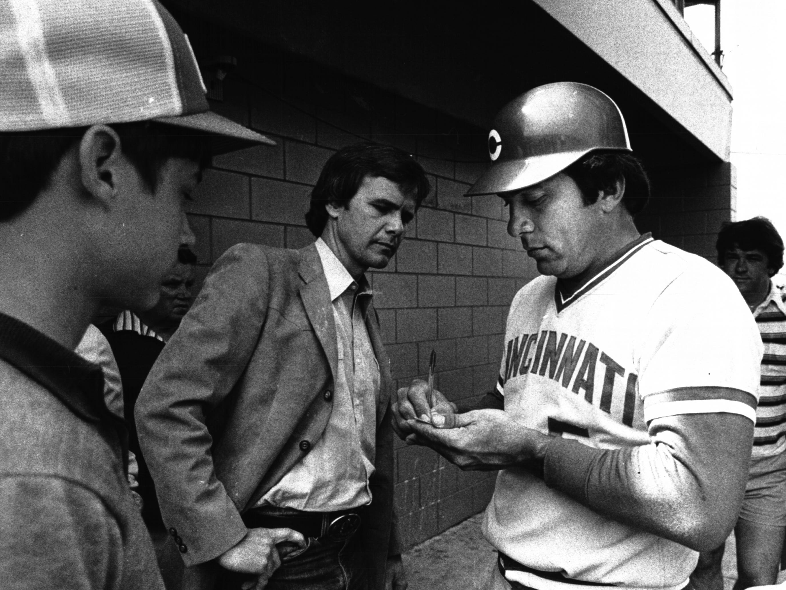 APRIL 7, 1980: Johnny Bench signs an autograph in the Al Lopez Field dugout during spring training this year as NBC Today Show host Tom Brokaw looks on. Bench is a popular figure with the national news media. Enquirer File Photo