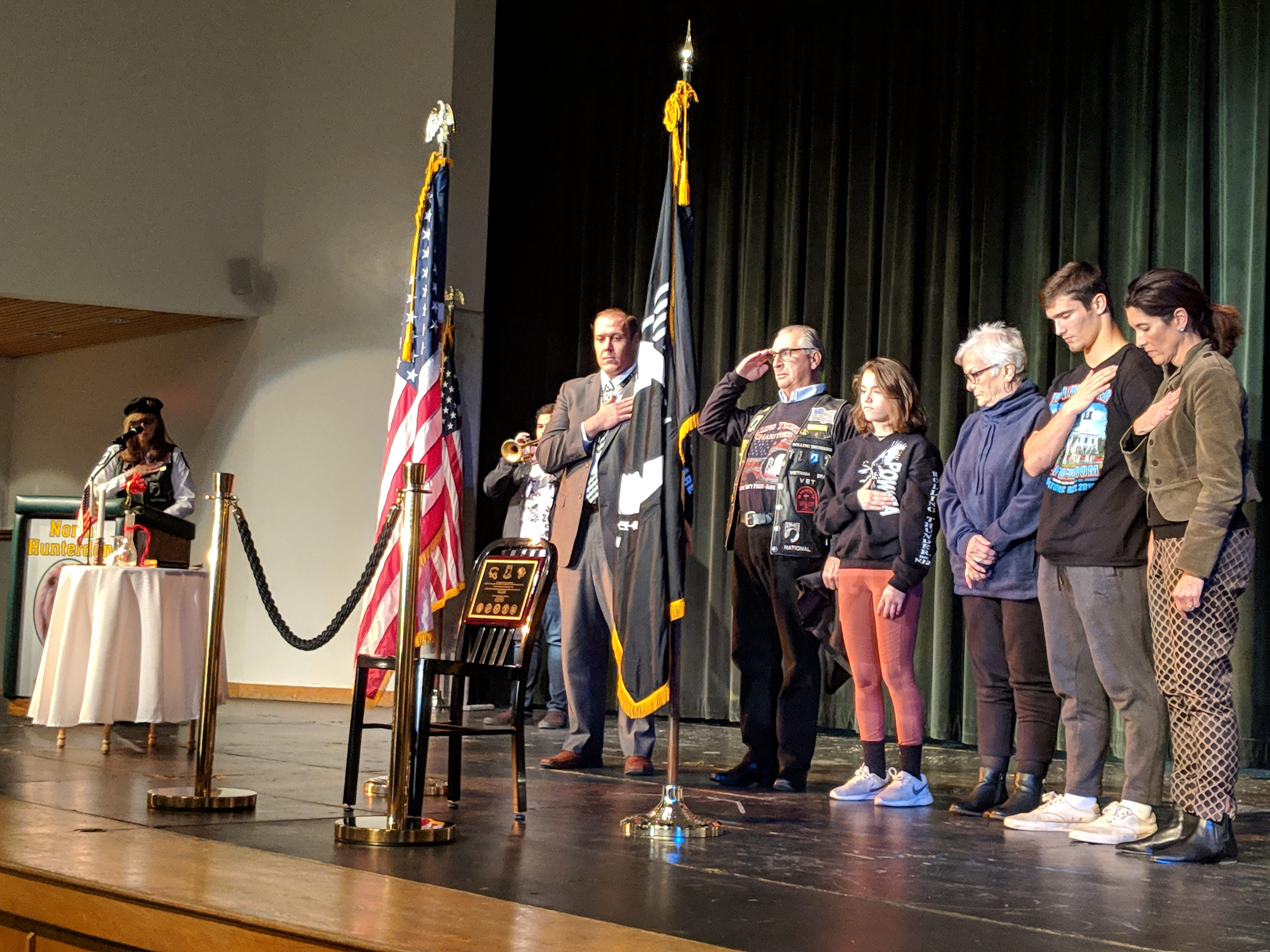 The chair and flags in the display case on 2nd floor; unveiling of the chair by Dr. Greg Cottrell, Gus Dante and the Dante Family; a moment of silence while senior Michael Kane of Franklin Township played taps after the cloth was taken off the chair.