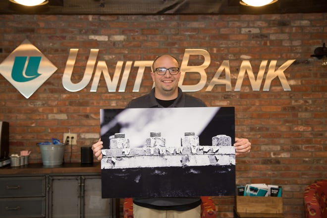 Nazareth photographer Dustin Coughlin, owner of Didco Photography, with one of his Steel Stacks photos purchased by Unity Bank through a program to support local artists.