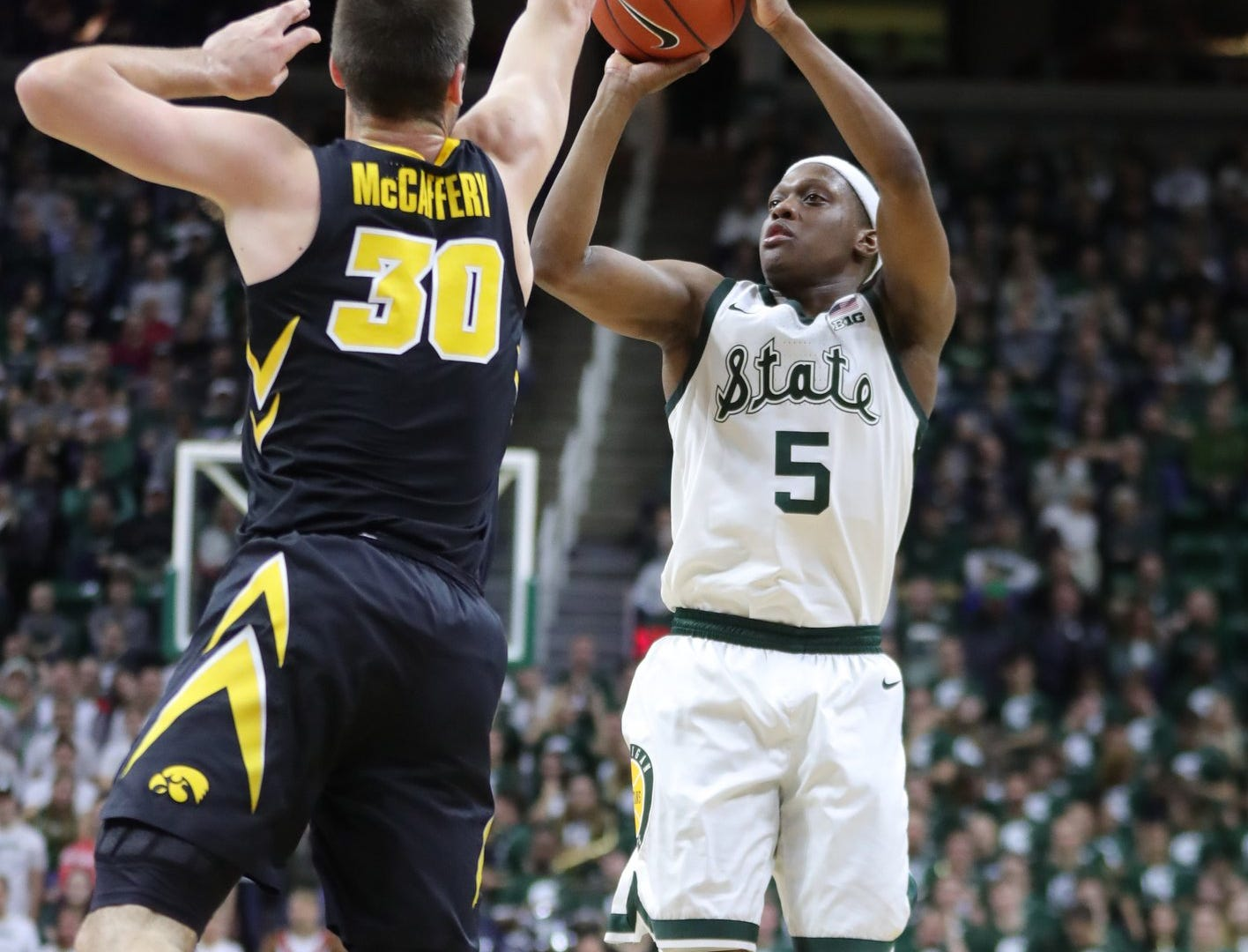 Michigan State guard Cassius Winston scores against Iowa guard Connor McCaffery during second half action Monday, December 3, 2018 at the Breslin Center in East Lansing, Mich.