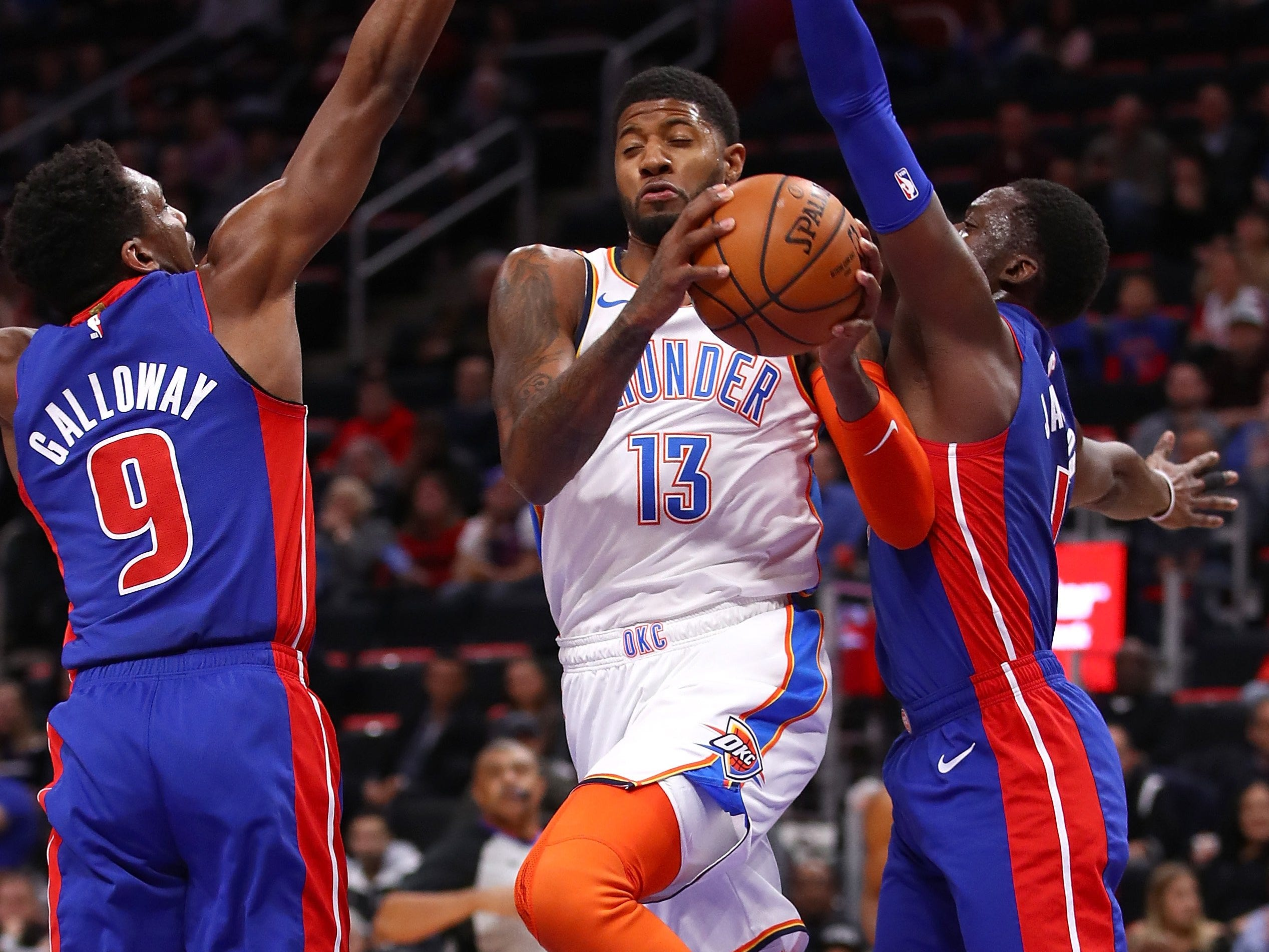 Paul George #13 of the Oklahoma City Thunder drives between Langston Galloway #9 and Reggie Jackson #1 of the Detroit Pistons during the first half at Little Caesars Arena on December 03, 2018 in Detroit, Michigan.