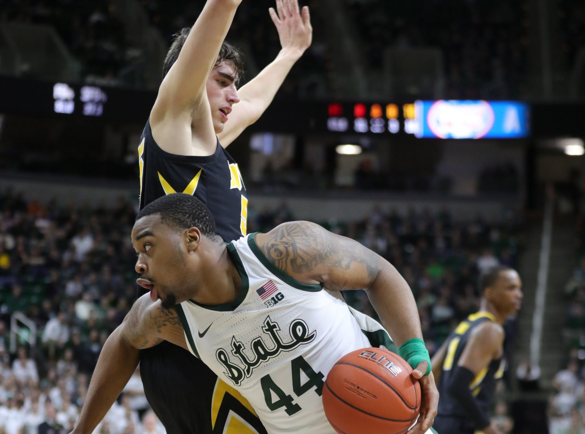 Michigan State forward Nick Ward drives against Iowa forward Luka Garza during second half action Monday, December 3, 2018 at the Breslin Center in East Lansing, Mich.