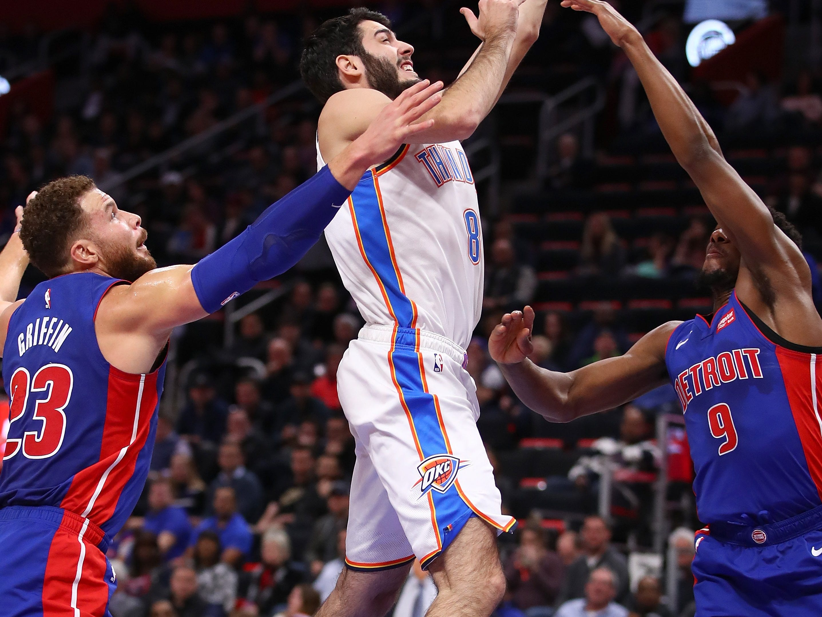 Alex Abrines #8 of the Oklahoma City Thunder tries to get a shot off between Langston Galloway #9 and Blake Griffin #23 of the Detroit Pistons during the first half at Little Caesars Arena on December 03, 2018 in Detroit, Michigan.