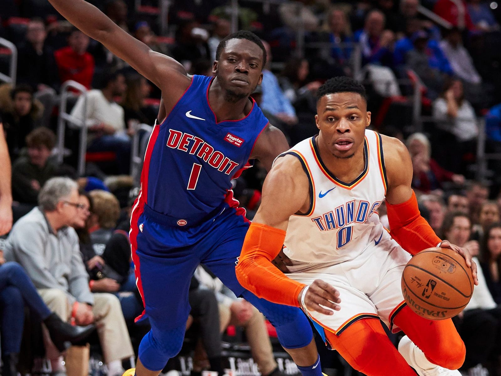Oklahoma City Thunder guard Russell Westbrook (0) dribbles past Detroit Pistons guard Reggie Jackson (1) in the first half at Little Caesars Arena.