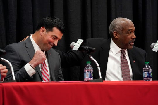 Ohio State athletic director Gene Smith pats offensive coordinator Ryan Day on the back during a news conference announcing both the retirement of coach Urban Meyer and the promotion to head coach of Day on Tuesday, Dec. 4, 2018, in Columbus, Ohio.