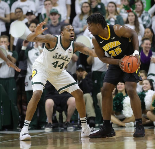 Michigan State Secretary of Defense Nick Ward defends Iowa forward Tyler Cook during the first half Monday 3 December 2018 at Breslin Center in East Lansing, Michigan.