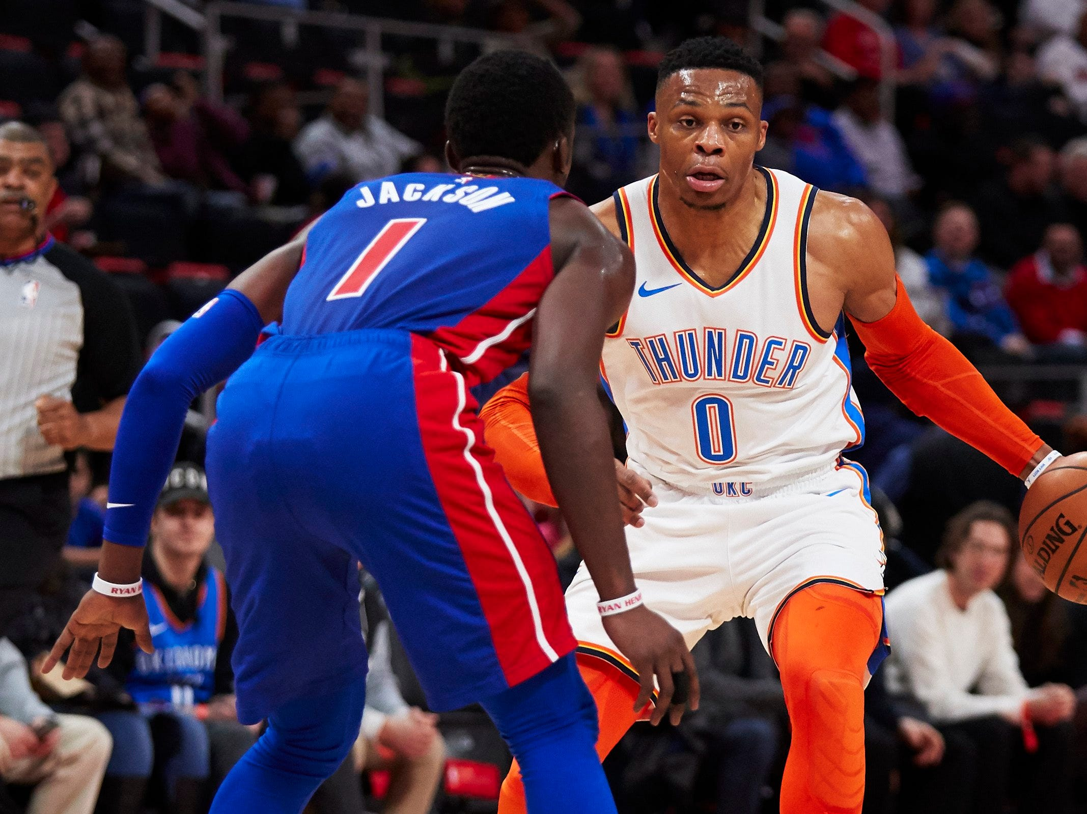 Oklahoma City Thunder guard Russell Westbrook (0) dribbles defended by Detroit Pistons guard Reggie Jackson (1) in the first half at Little Caesars Arena.