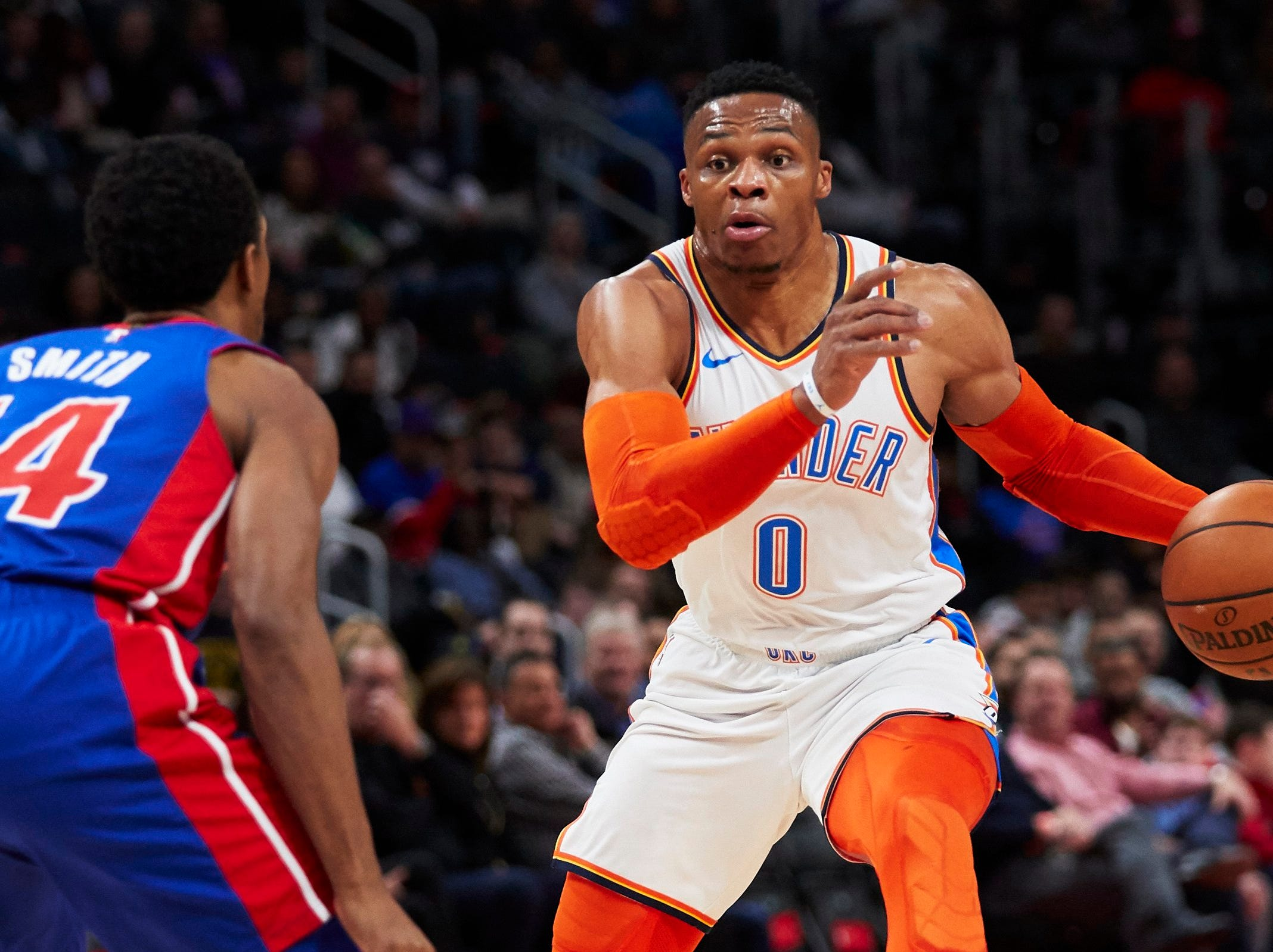 Oklahoma City Thunder guard Russell Westbrook (0) dribbles defended by Detroit Pistons guard Ish Smith (14) in the first half at Little Caesars Arena.