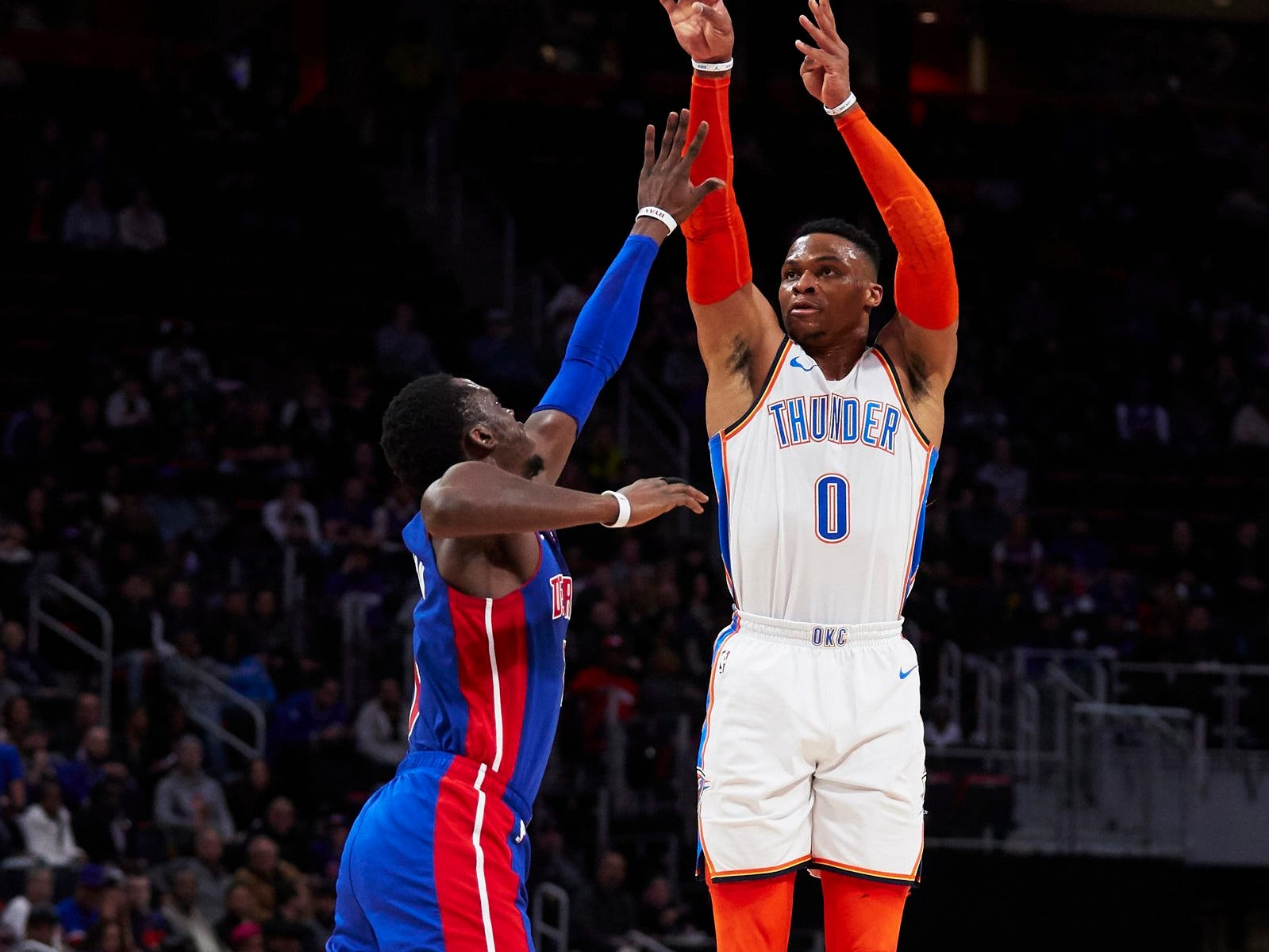 Oklahoma City Thunder guard Russell Westbrook (0) shoots over Detroit Pistons guard Reggie Jackson (1) in the first half at Little Caesars Arena.
