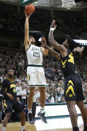 Michigan State forward Kenny Goins scores against Iowa forward Tyler Cook during second half action Monday, December 3, 2018 at the Breslin Center in East Lansing, Mich.