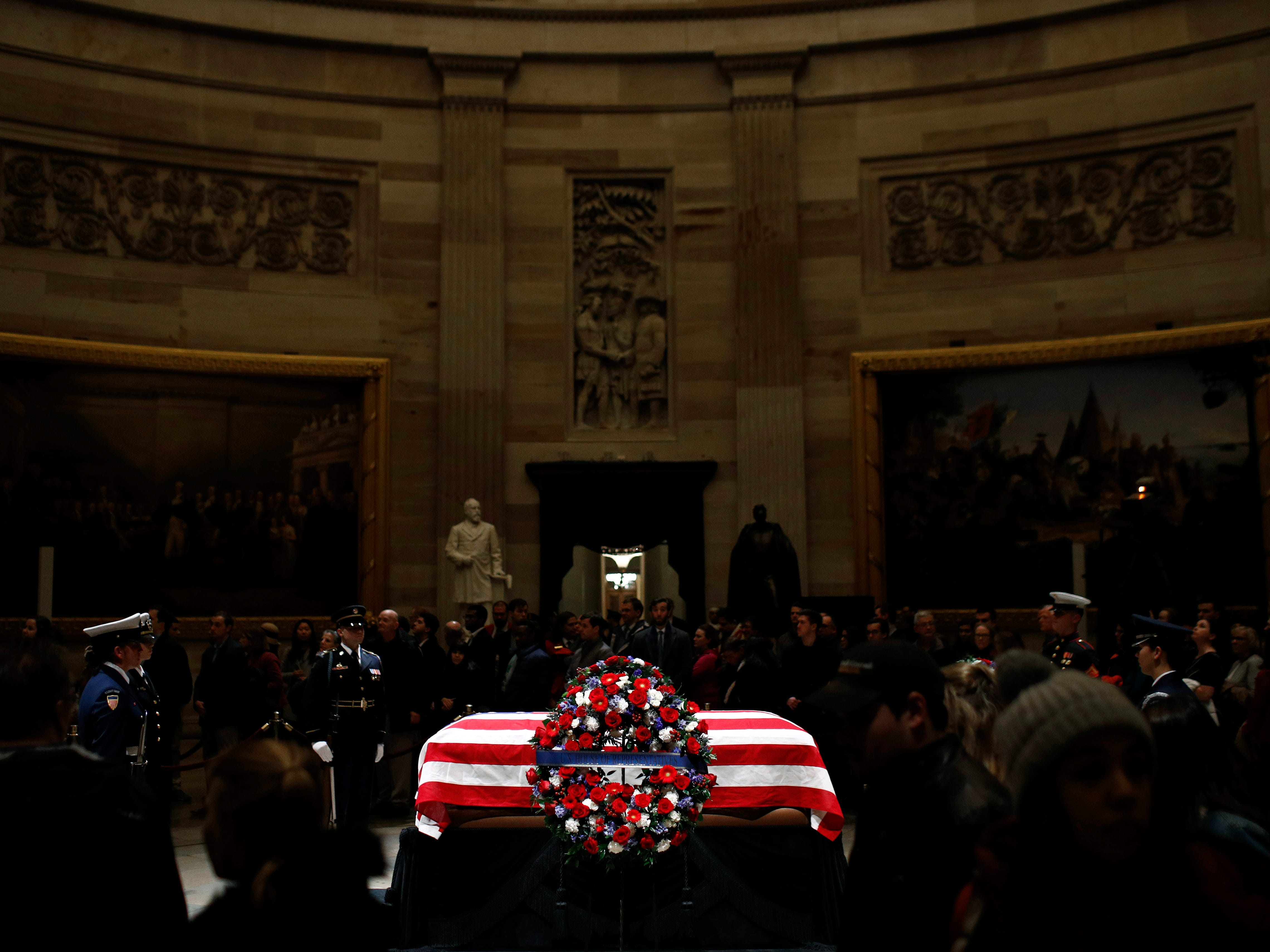 Visitors file past the flag-draped casket of former President George H.W. Bush as he lies in state in the Capitol Rotunda in Washington, Monday, Dec. 3, 2018.