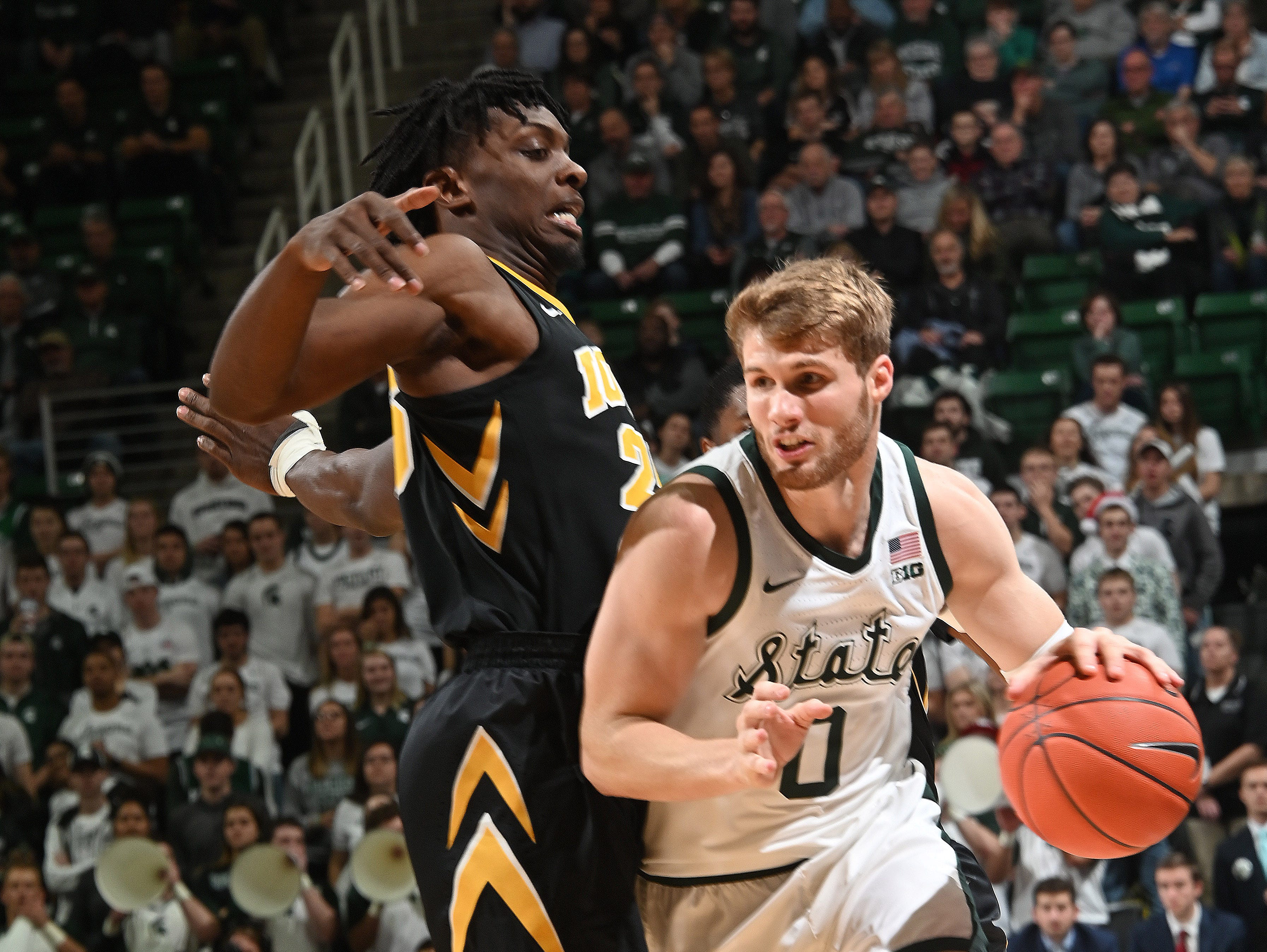 Spartan Kyle Ahrens muscles his way past Tyler Cook on his way to the basket in the first half.