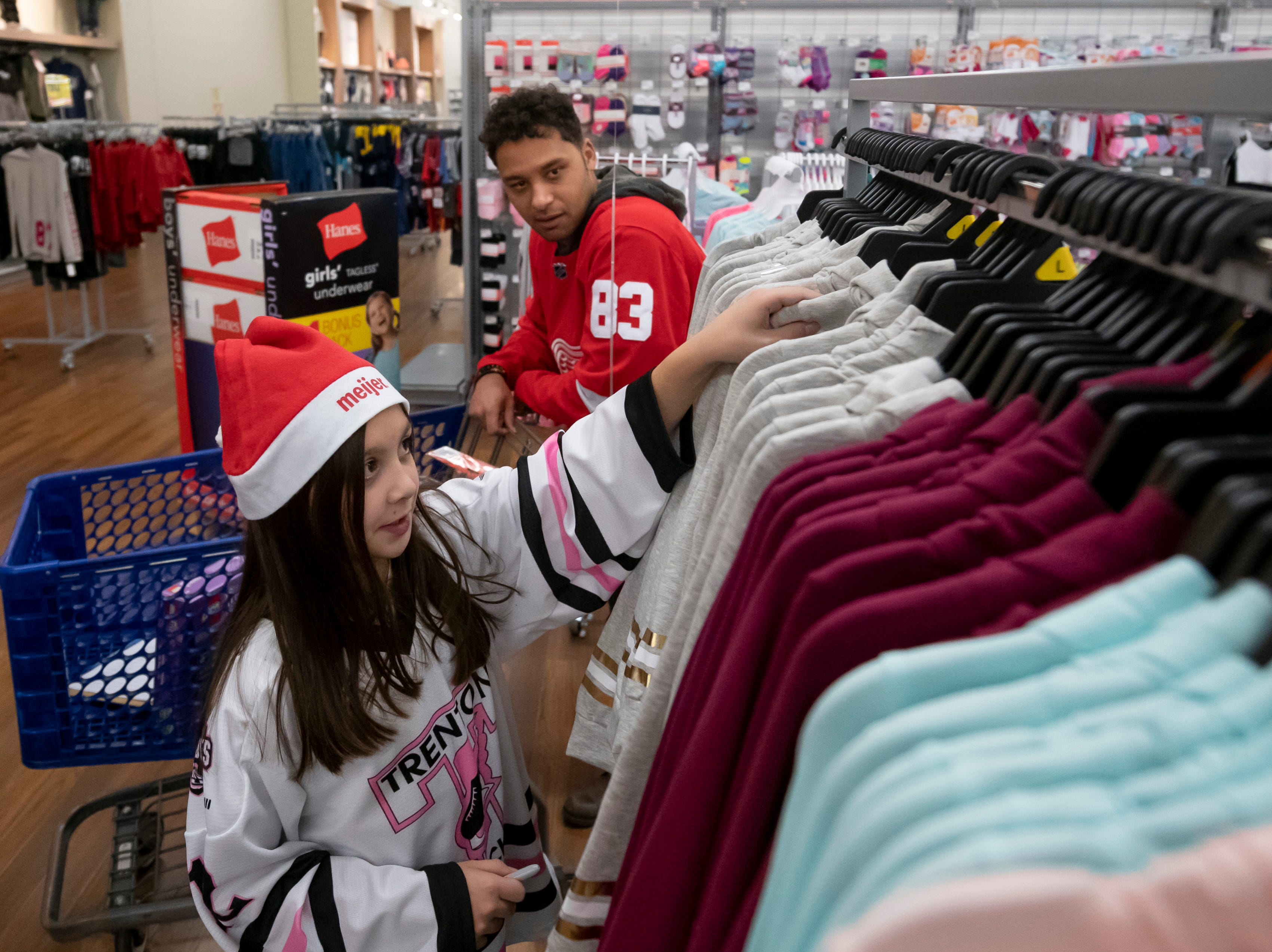 (From left) Nine-year-old Miranda Alcala, and defenseman Trevor Daley shop for clothes during the Detroit Red Wings annual Hometown Holiday Assist shopping spree.