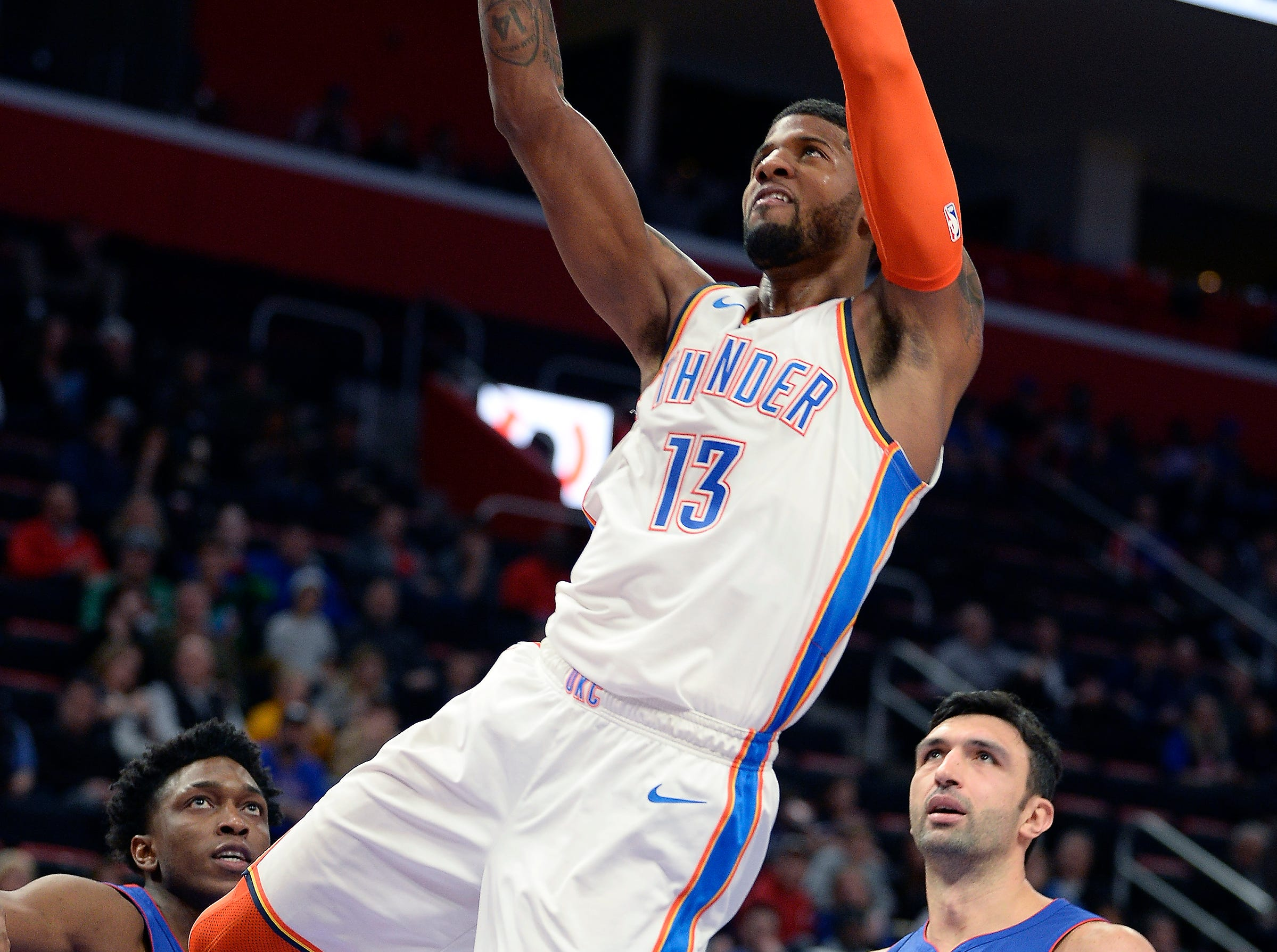 Thunder's Paul George dunks over Pistons' l-r, Stanley Johnson and ZaZa Pachulia in the third quarter. George had 17 points and 10 rebounds.