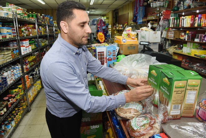 Mohamed Gee, of Hamtramck City Market, stocks shelves at the family owned store in Hamtramck on Tuesday, The market has seen a sharp drop in business since the announcement of job cuts at General Motors.