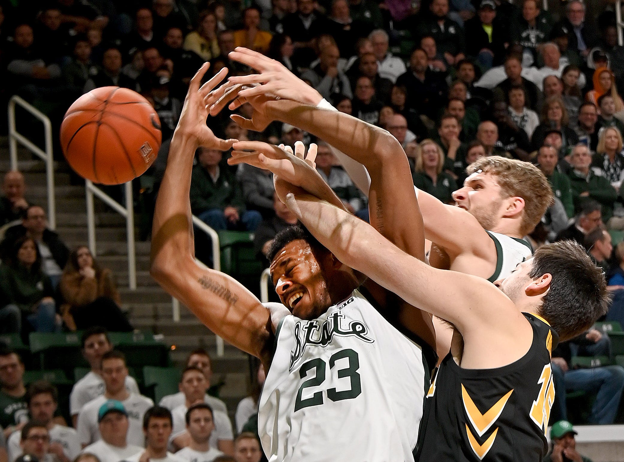 Xavier Tillman (23) gets fouled under the Spartan basket while battling for a rebound in the second half.