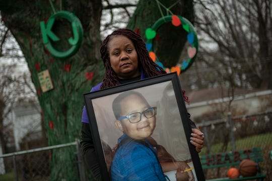 LaSondra Singleton holds a photo of her son Kenneth Gross Jr. while standing in front of a tree that was decorated in her son's honor at her Warren home.