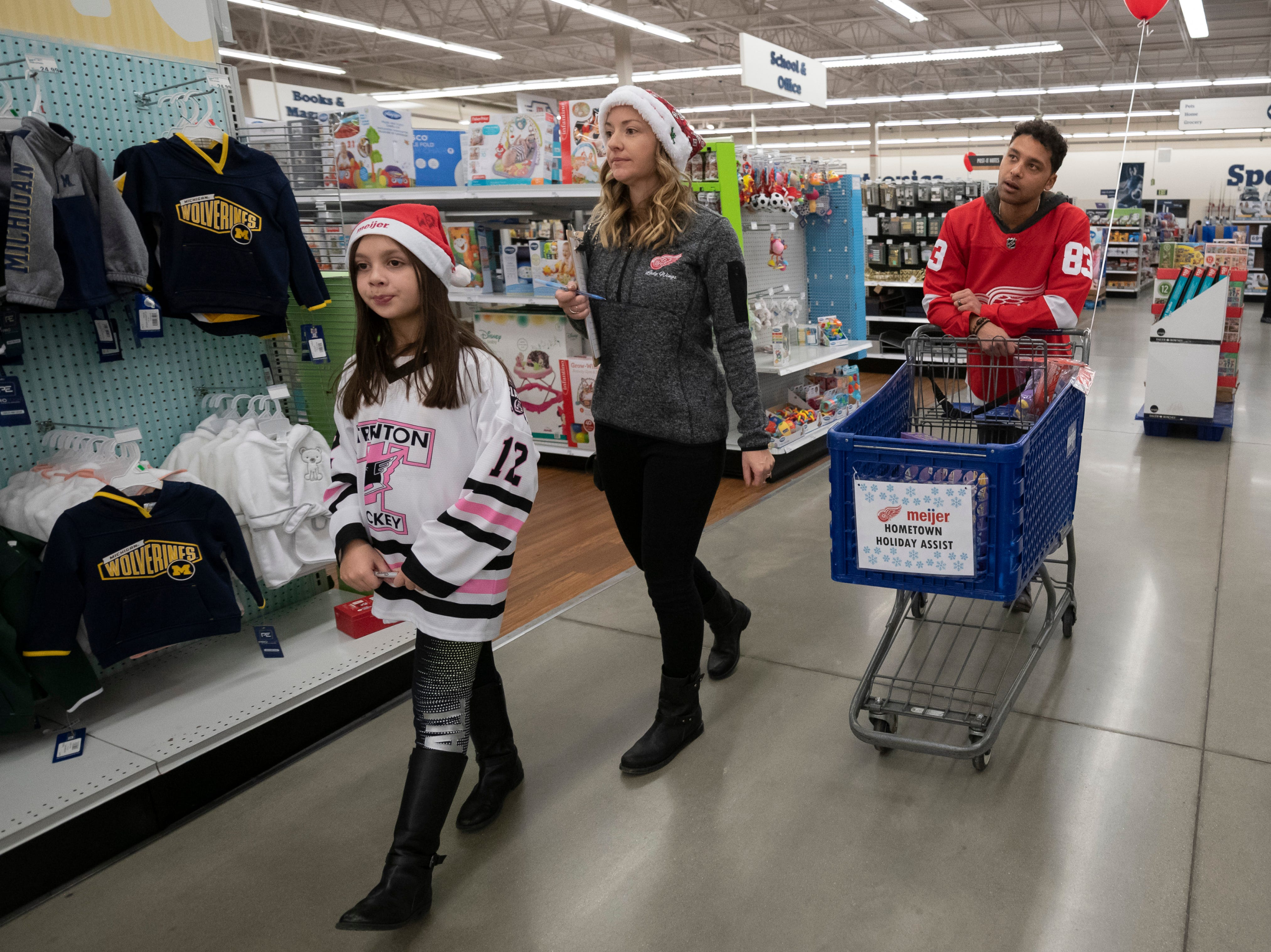 (From left) Nine-year-old Miranda Alcala, of Detroit, Kirsty Daley, and her husband Detroit defenseman Trevor Daley shop for clothes.