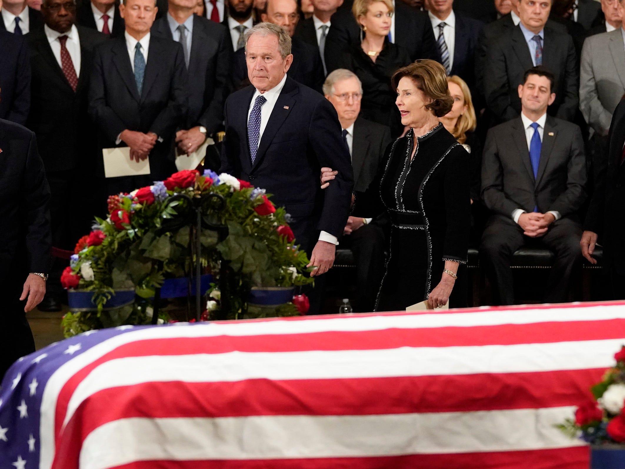 Former President George W. Bush and former first lady Laura Bush walk past the flag-draped casket of former President George H.W. Bush in the Capitol Rotunda, Monday, Dec. 3, 2018 in Washington.